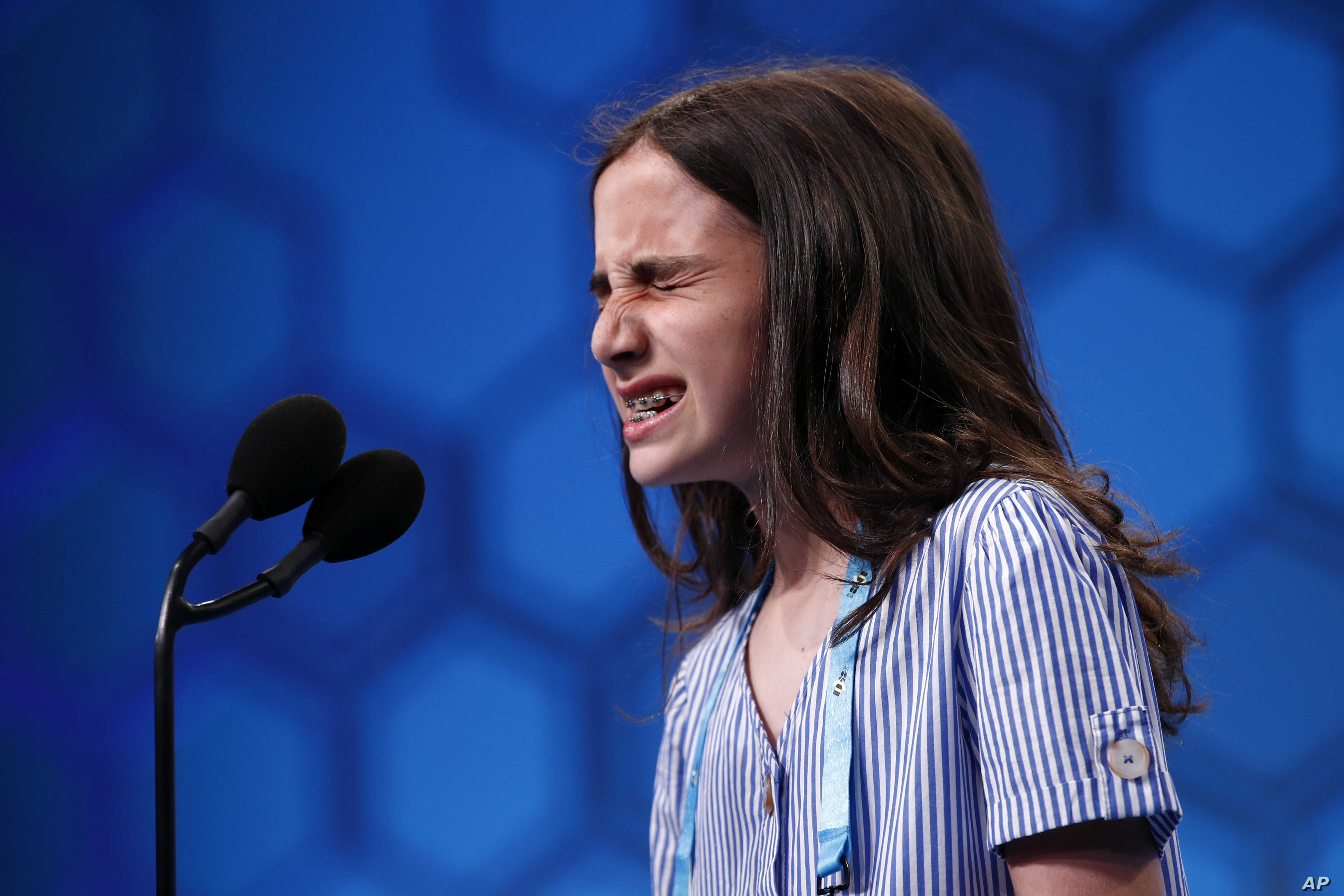 Caroline Kovacs, 10, of Hoboken, N.J., reacts as she spells out a word in the third round of the Scripps National Spelling Bee, May 29, 2019, in Oxon Hill, Md.