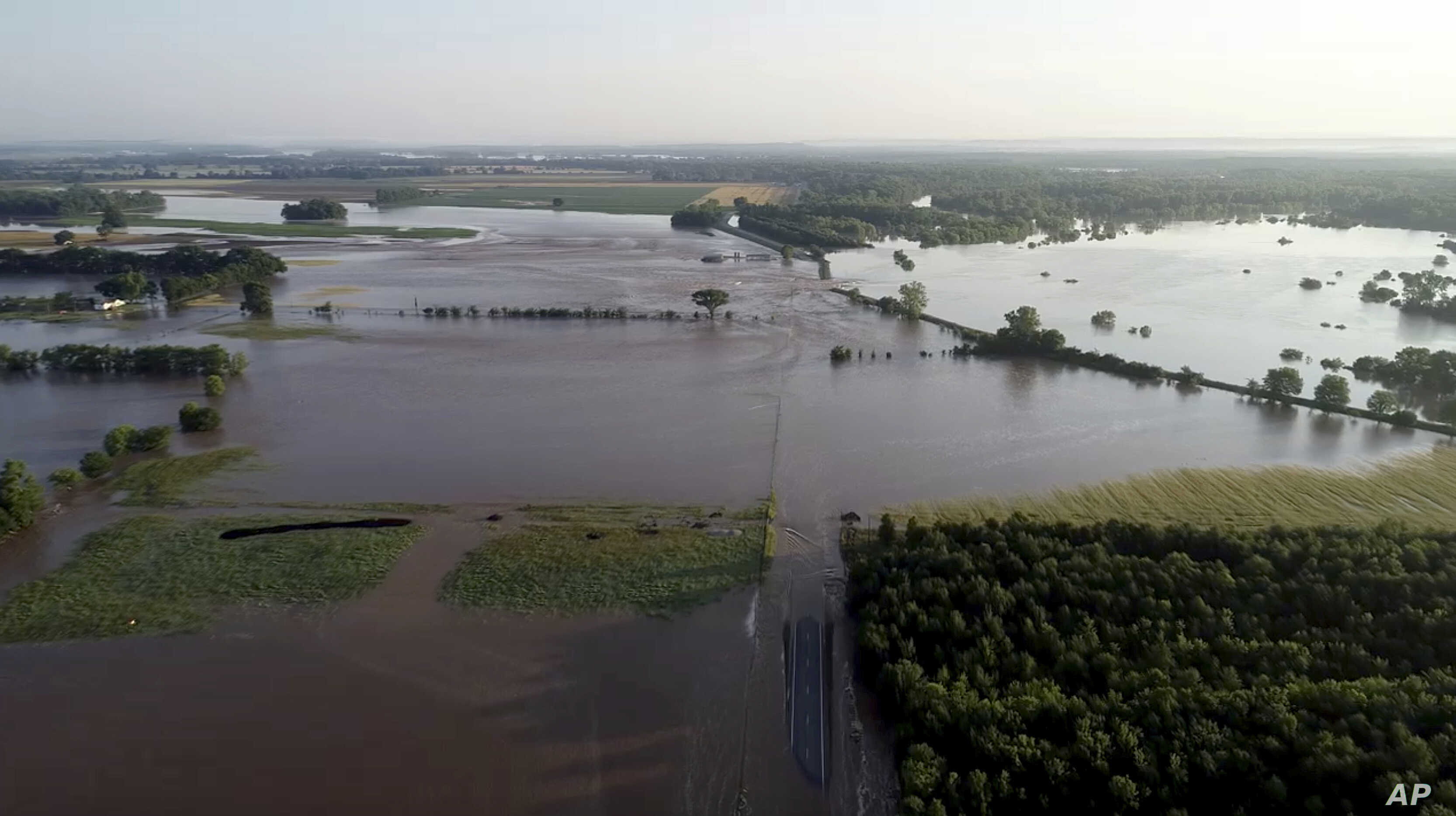 In this aerial image provided by Yell County Sheriff's Department water rushes through the levee along Arkansas River in Dardanelle, Ark., May 31, 2019. Officials say the levee breached early Friday at Dardanelle, about 60 miles northwest of Little R...