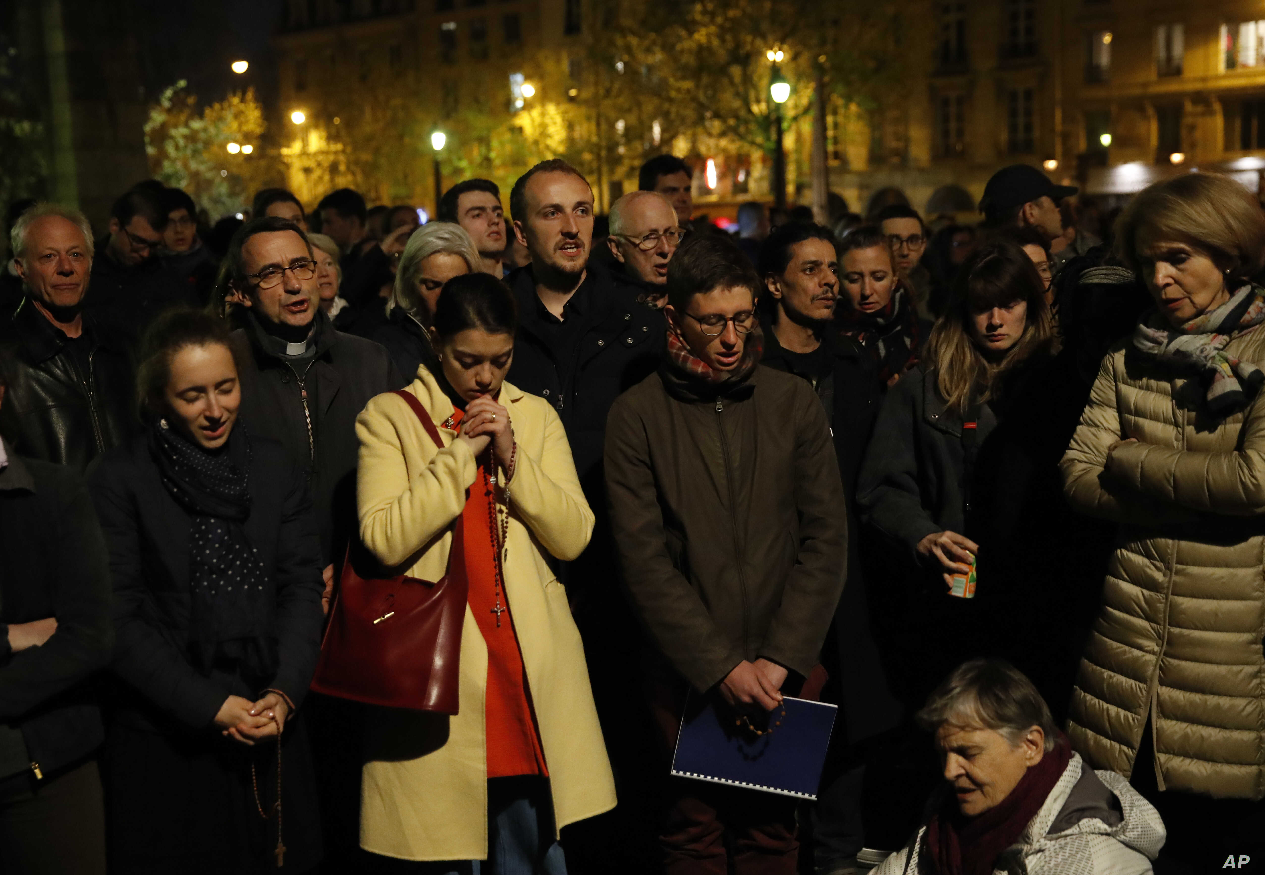 People pray as Notre Dame cathedral is burning in Paris, Monday, April 15, 2019.