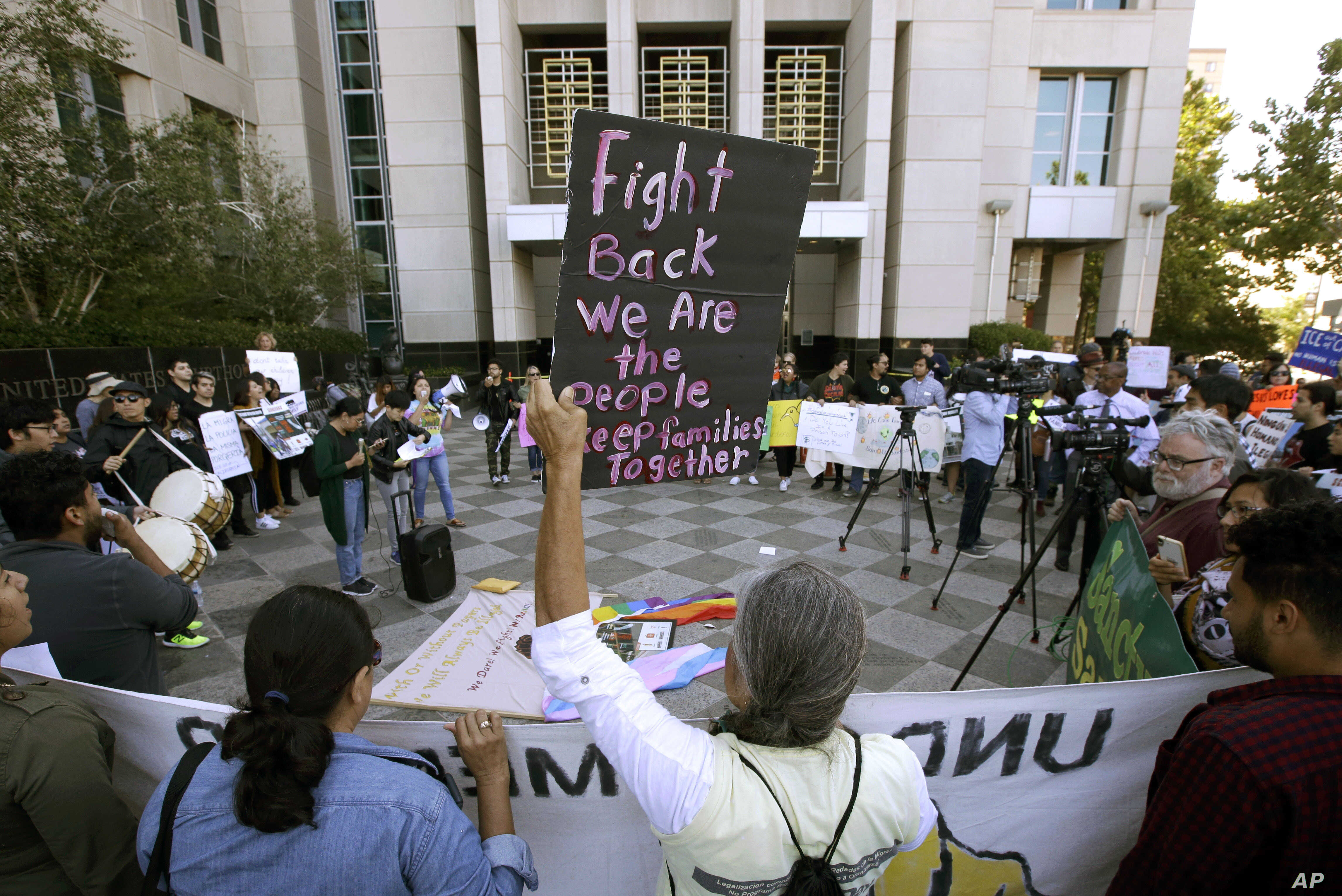 FILE - In this June 20, 2018, photo, protesters demonstrate outside the federal courthouse in Sacramento, Calif., where a judge heard arguments over the U.S. Justice Department's request to block three California laws that extend protections to peopl...