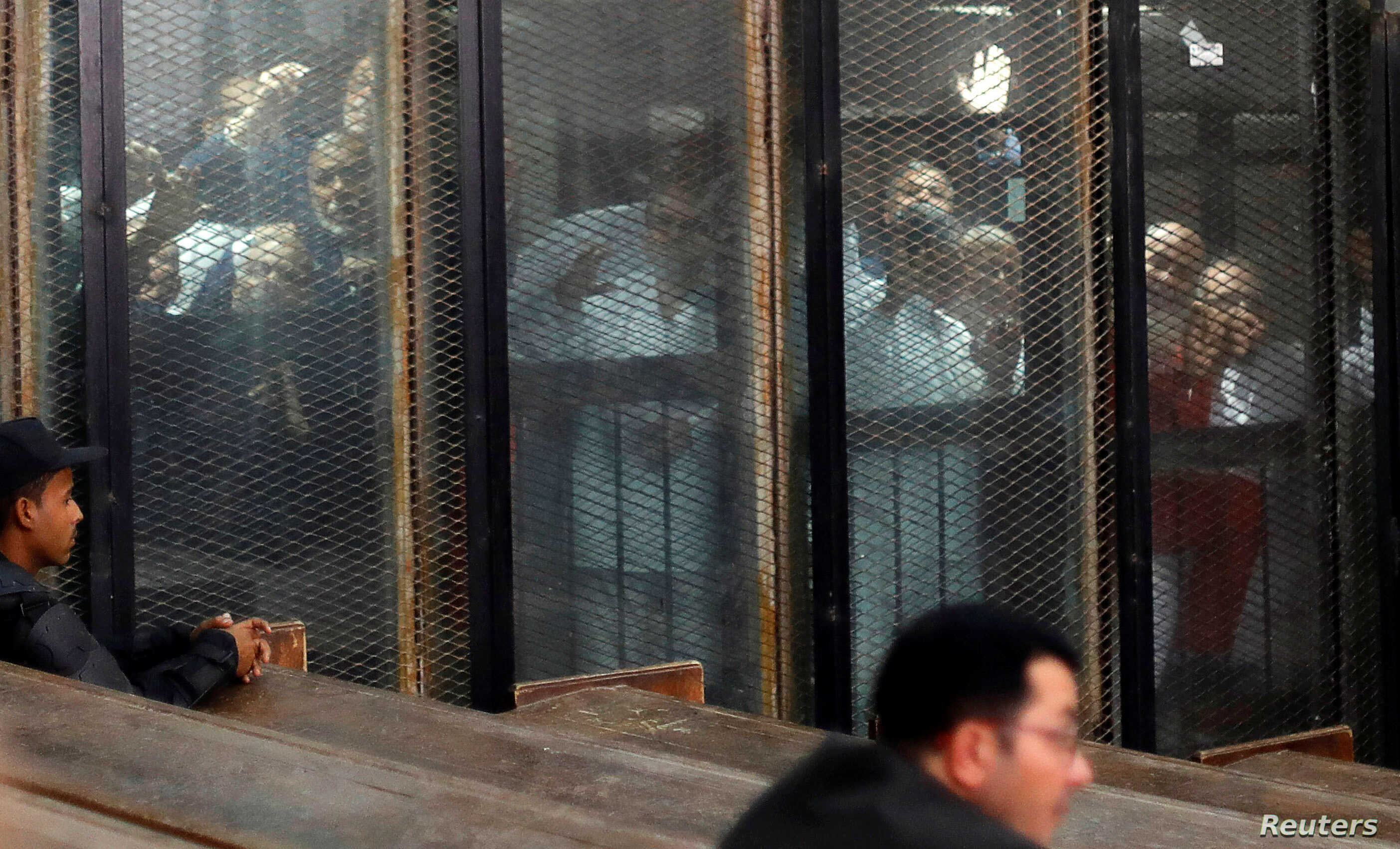 FILE - Muslim Brotherhood members are seen behind bars during a court session in Cairo, Egypt, Dec. 2, 2018.