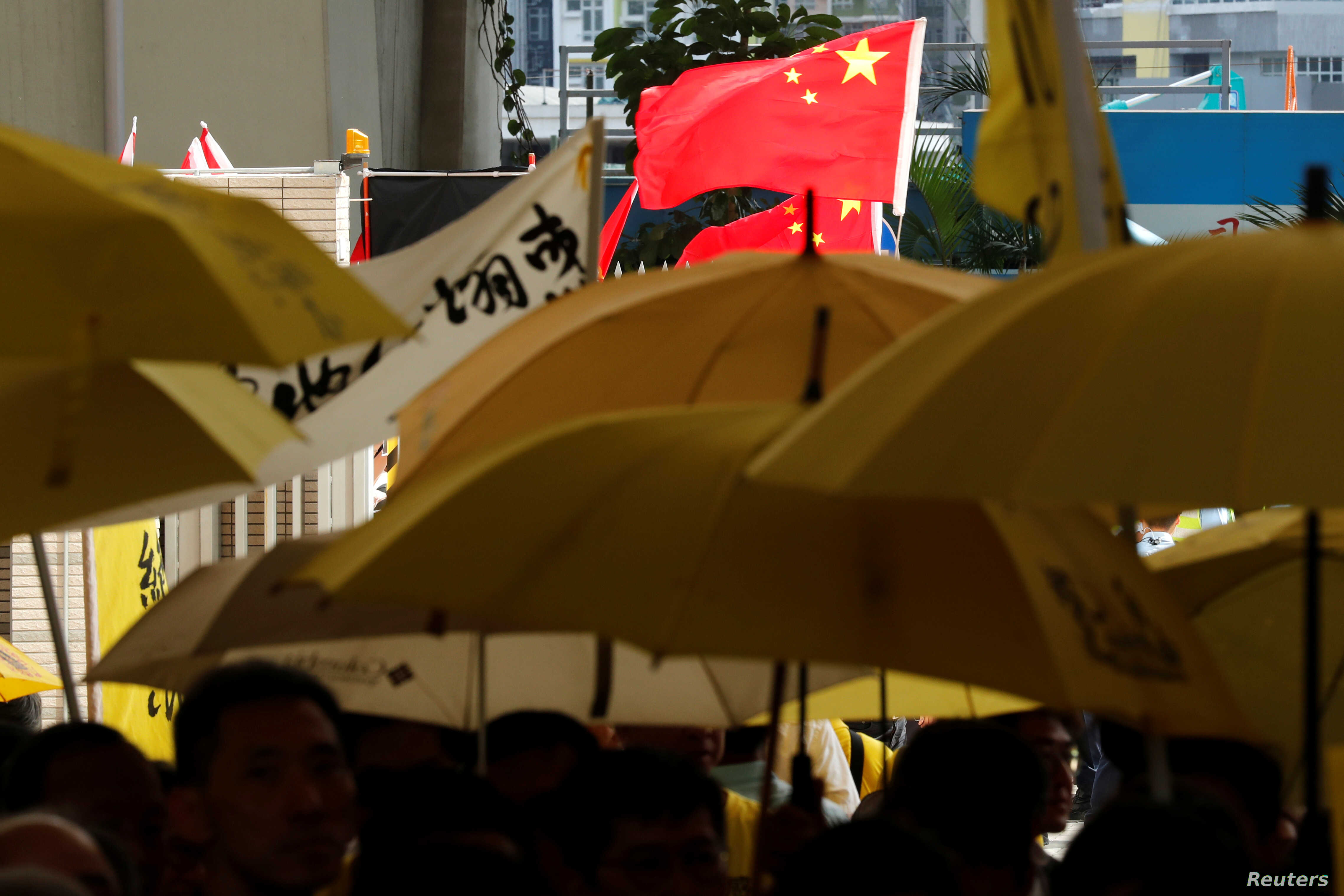 Pro-China supporters wave Chinese national flag as pro-democracy supporters hold yellow umbrellas to support leaders of Occupy Central activists outside the court, in Hong Kong, China, April 24, 2019.