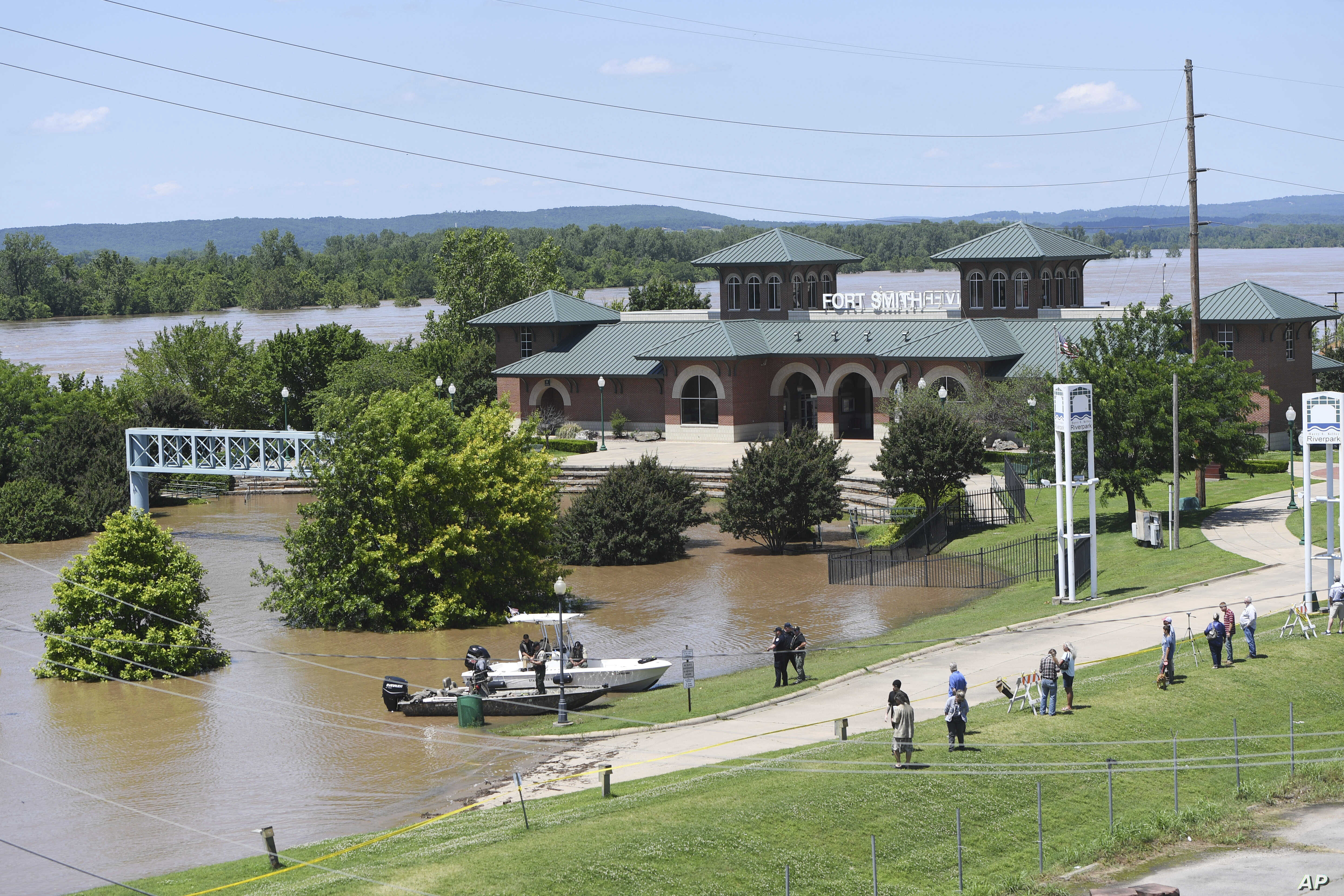 Local residents watch as the Arkansas River floods Harry E. Kelley River Park, May 30, 2019, in Fort Smith, Ark.