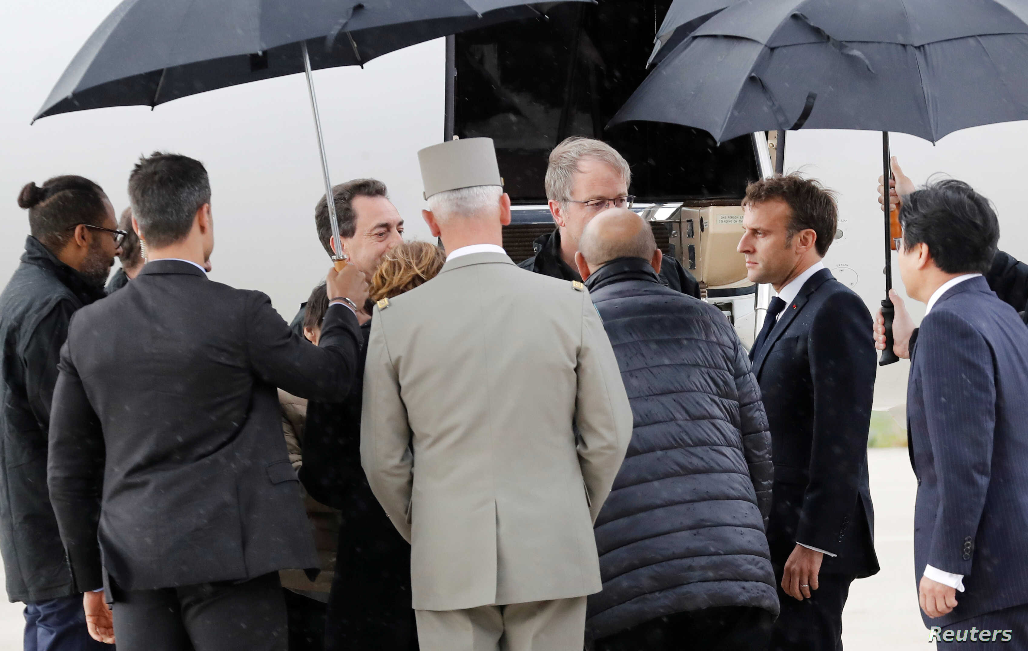 French President Emmanuel Macron greets hostages who were freed by special forces in Burkina Faso upon their arrival at the Villacoublay airport, in Velizy-Villacoublay, France, May 11, 2019.