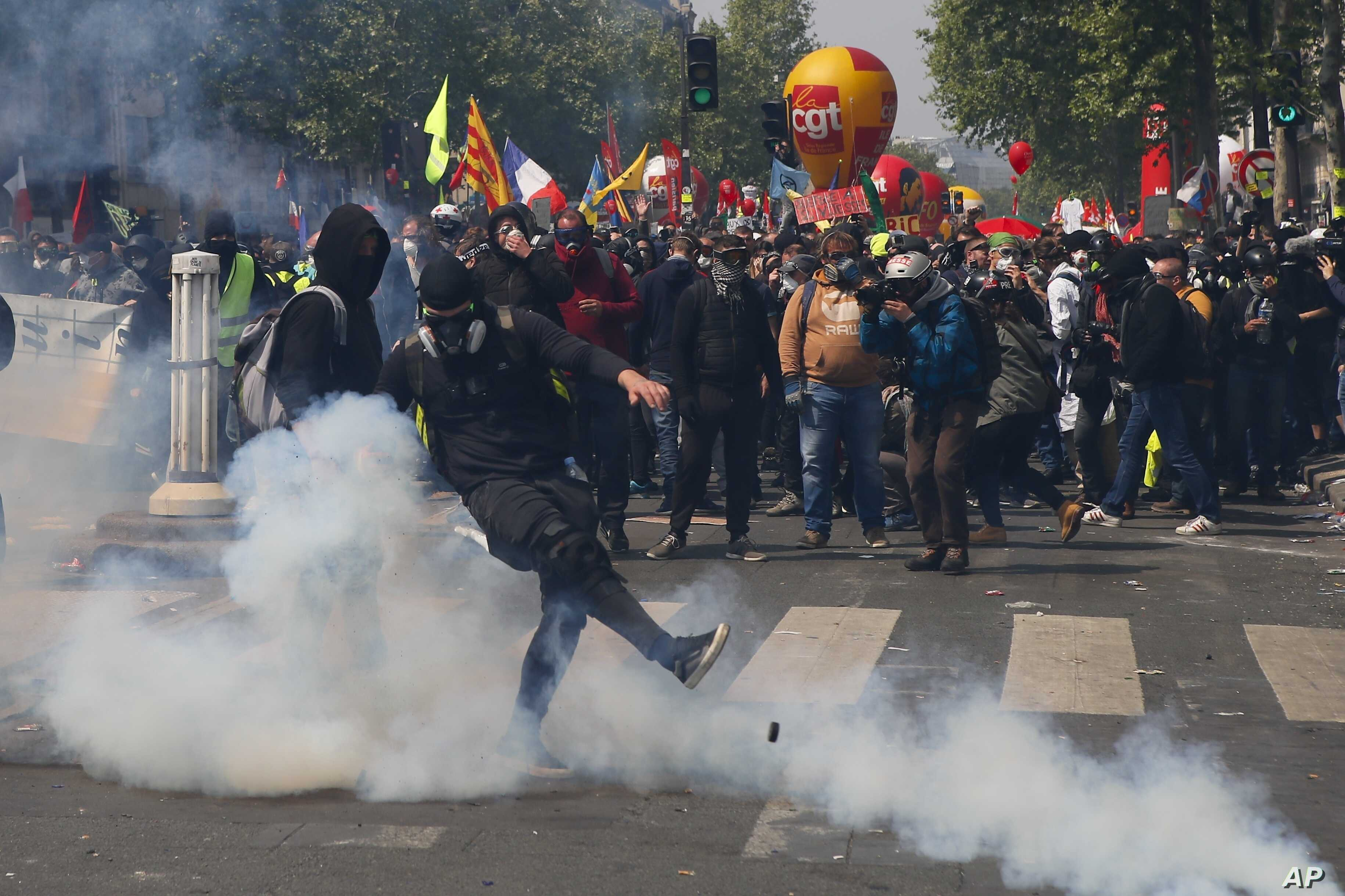 An activist kicks away a tear gas canister during a May Day demonstration in Paris, Wednesday, May 1, 2019.