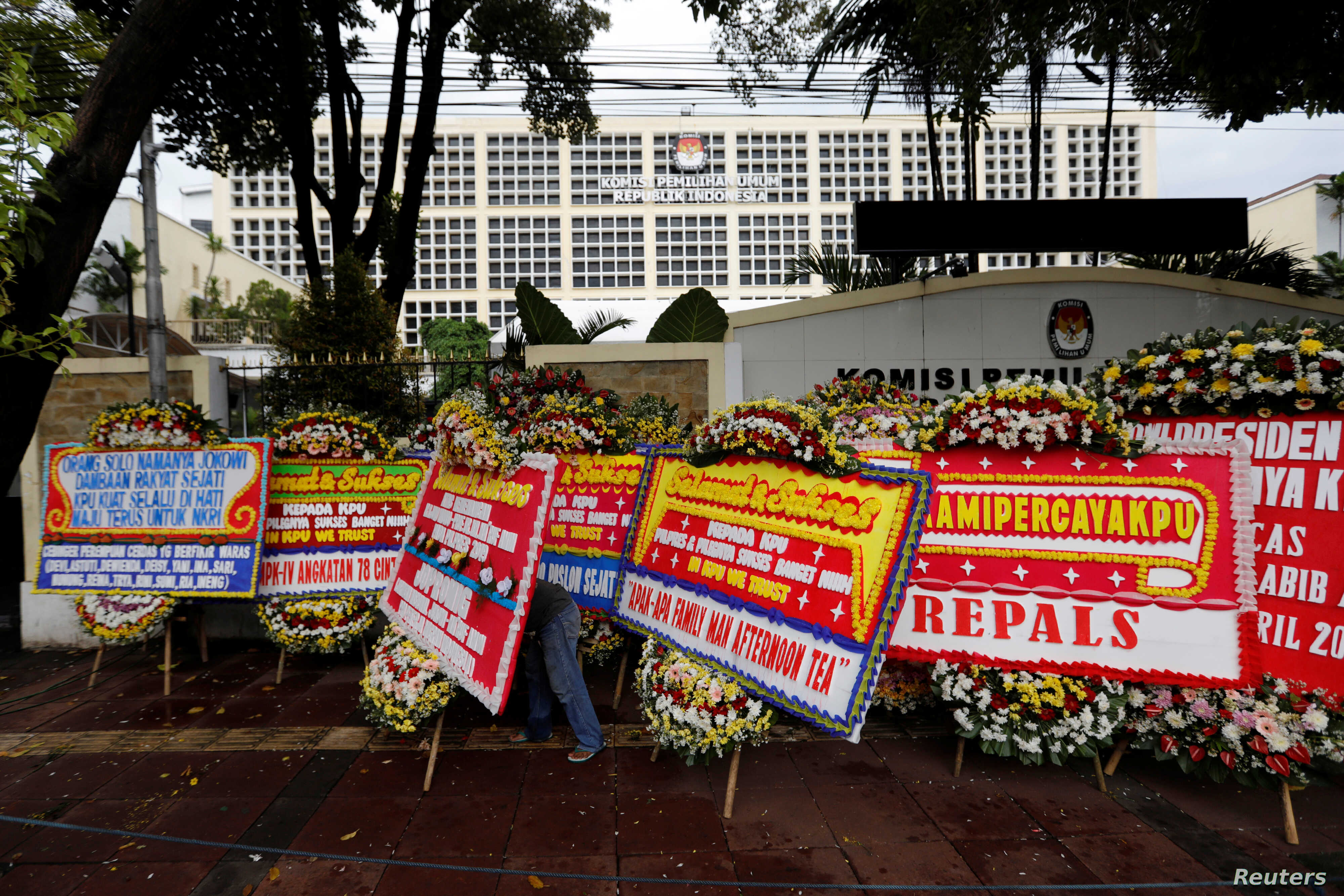 FILE - A worker arranges flower wreaths and congratulatory boards from people after this week's election outside General Election Commission (KPU) headquarters in Jakarta, Indonesia, Apr. 21, 2019.