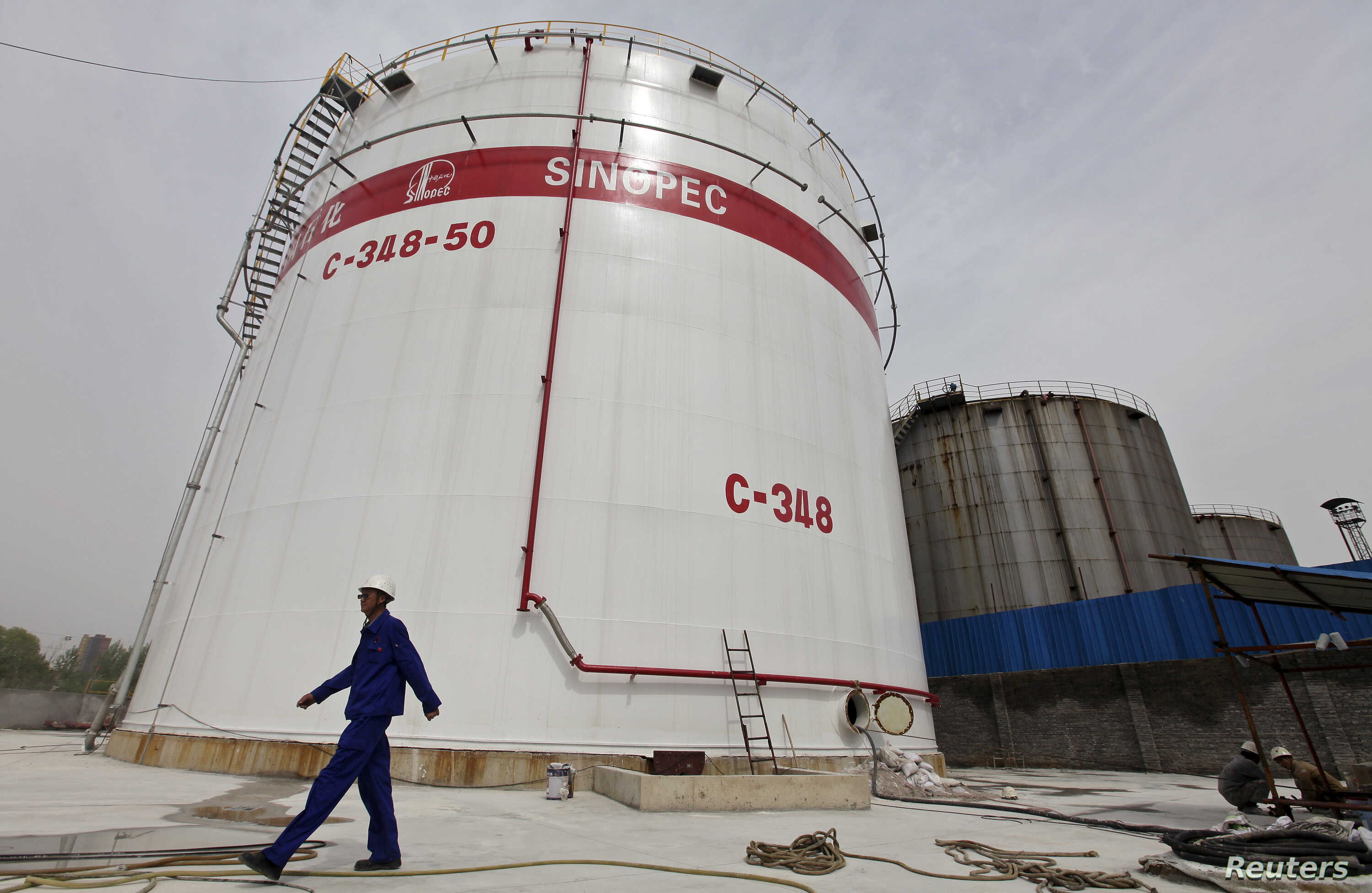 FILE - An employee walks past oil tanks at a Sinopec refinery in Wuhan, Hubei province April 25, 2012.