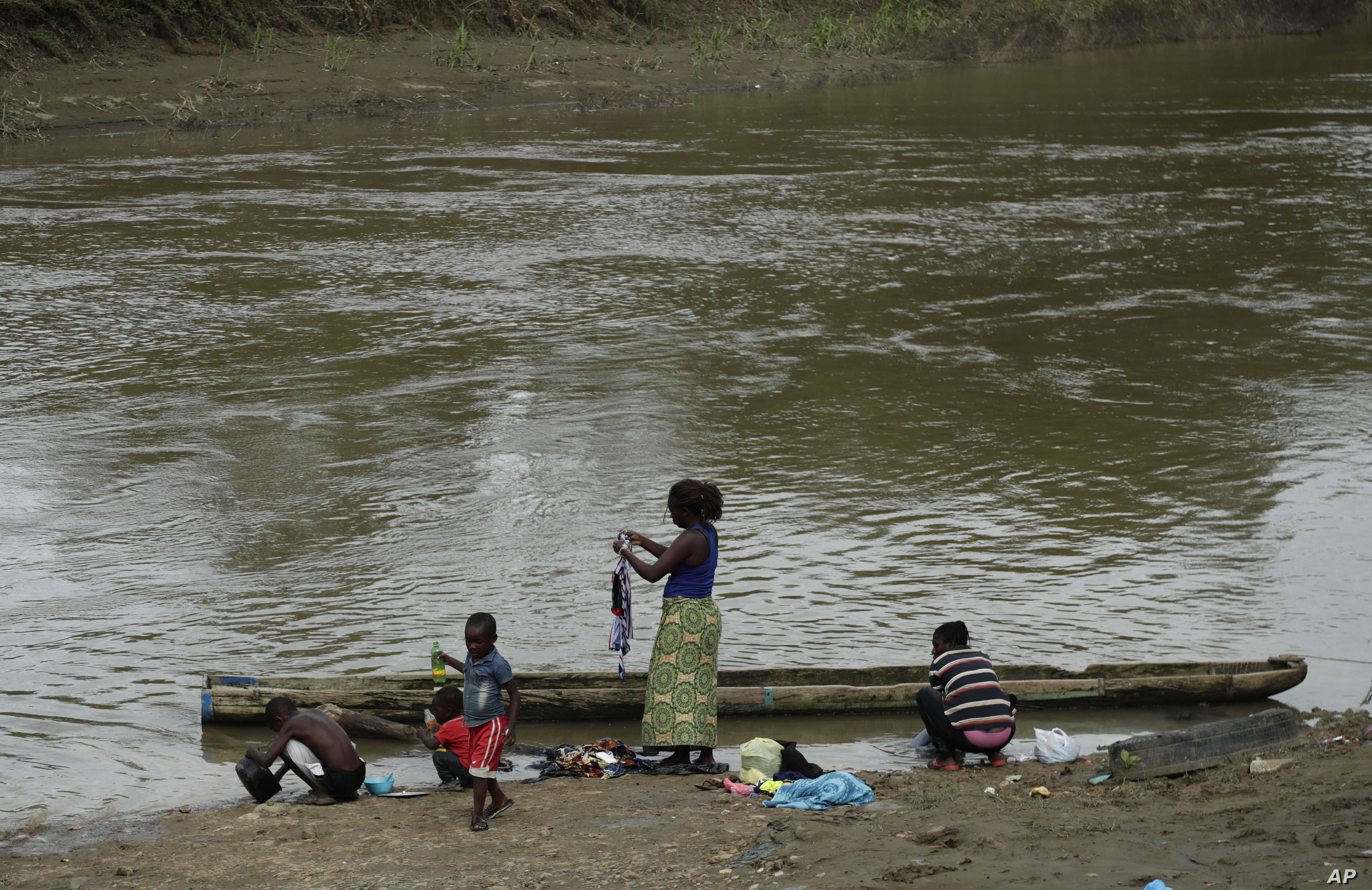 Migrants wash their clothes on the Chucunaque river on May 10, 2019, in Peñitas, Darien Province, Panama.
