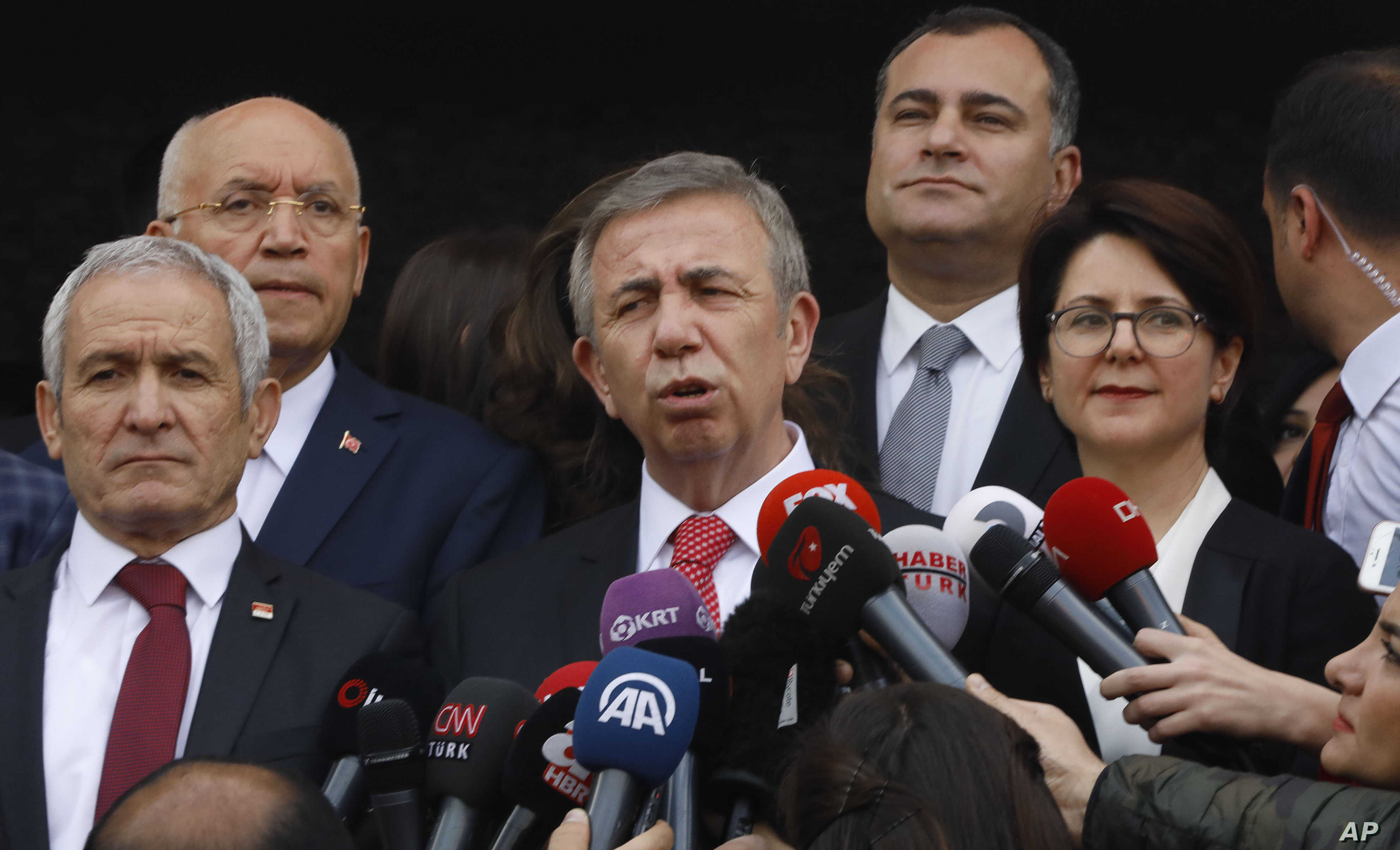 The main Turkish opposition candidate for the country's capital Ankara, Mansur Yavas, center, speaks to the media after he received the document confirming him as new mayor, from Bahattin Ozbas the head of the election board, in Ankara on April 8, 20...
