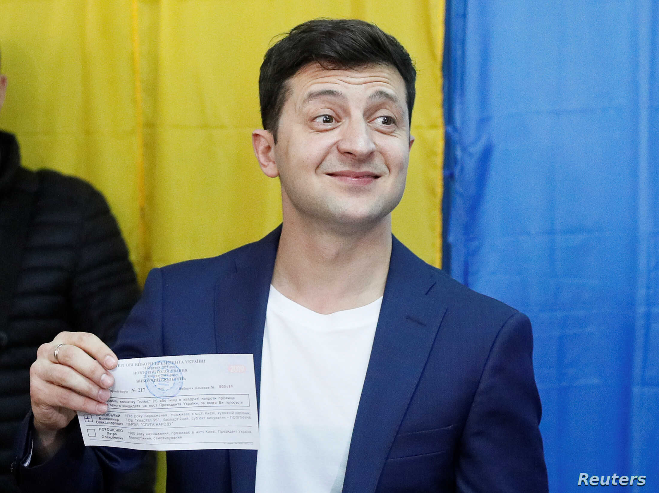 Ukrainian presidential candidate Volodymyr Zelenskiy holds up his ballot while standing in front of the media at a polling station during the second round of a presidential election in Kyiv, Ukraine, April 21, 2019.