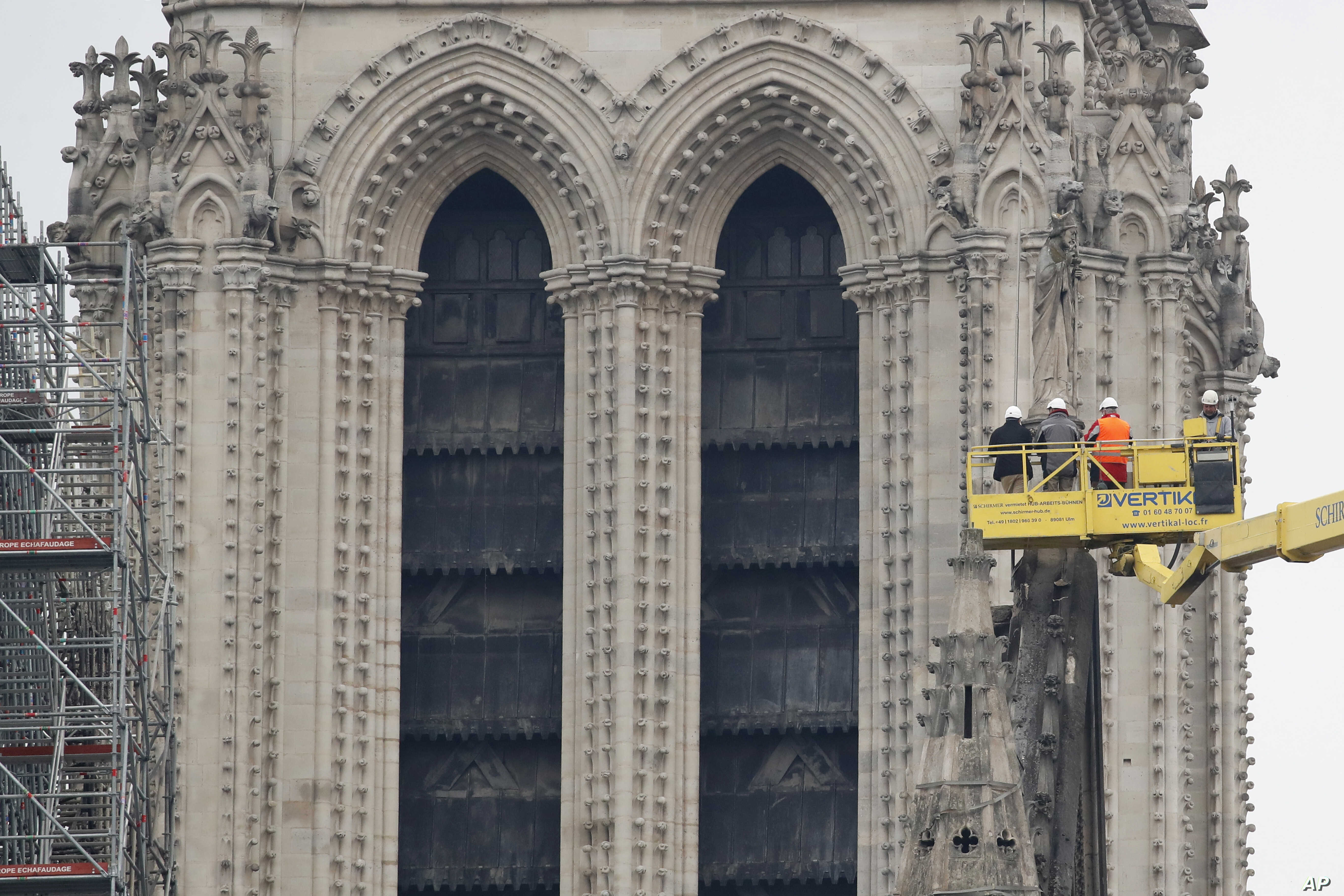 A crane lifts experts as they inspect the damaged Notre Dame cathedral after the fire in Paris, Apr. 16, 2019.