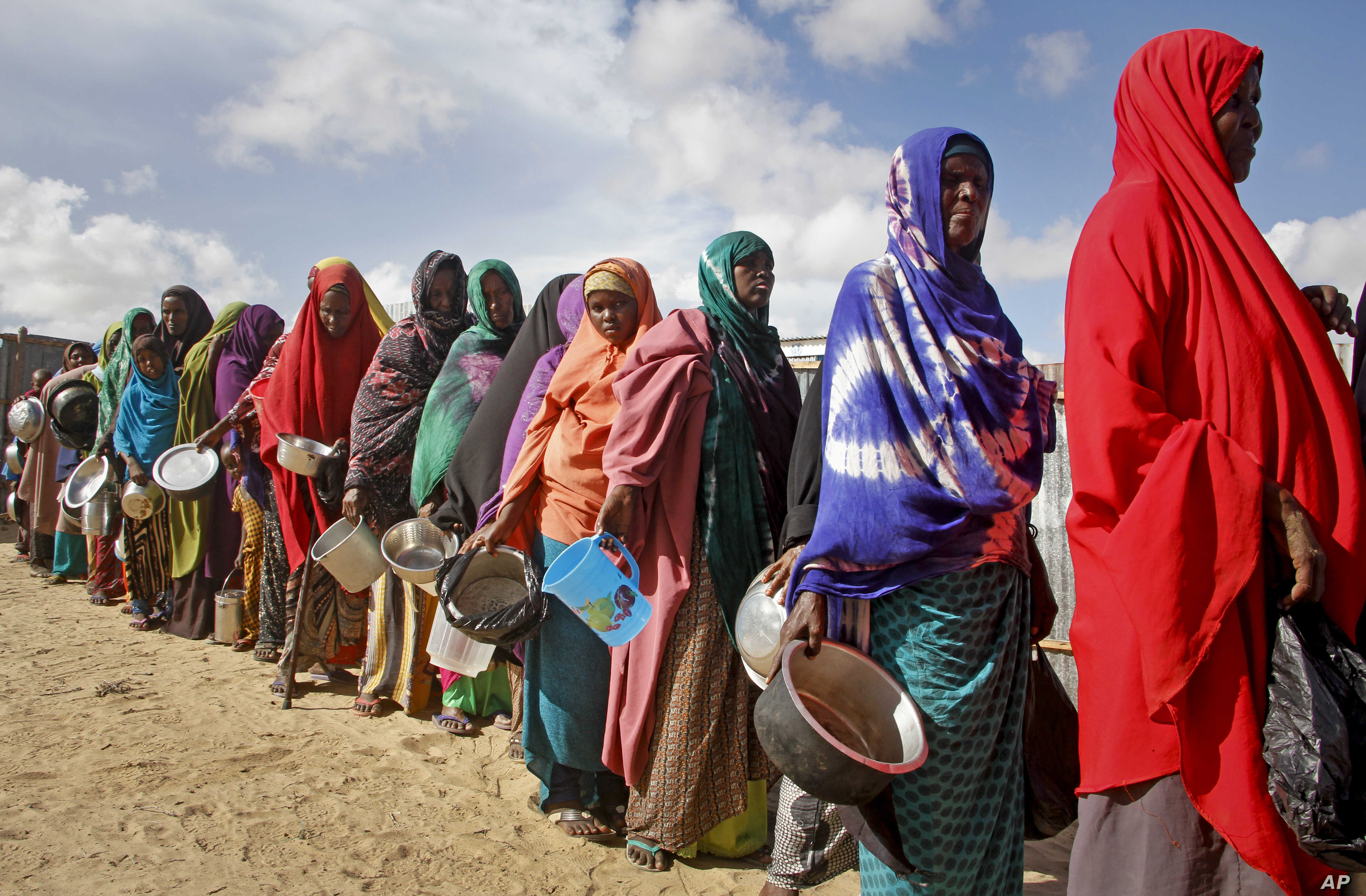 Women who fled drought queue to receive food distributed by local volunteers at a camp for displaced persons in the Daynile neighborhood on the outskirts of Mogadishu, in Somalia, May 18, 2019.