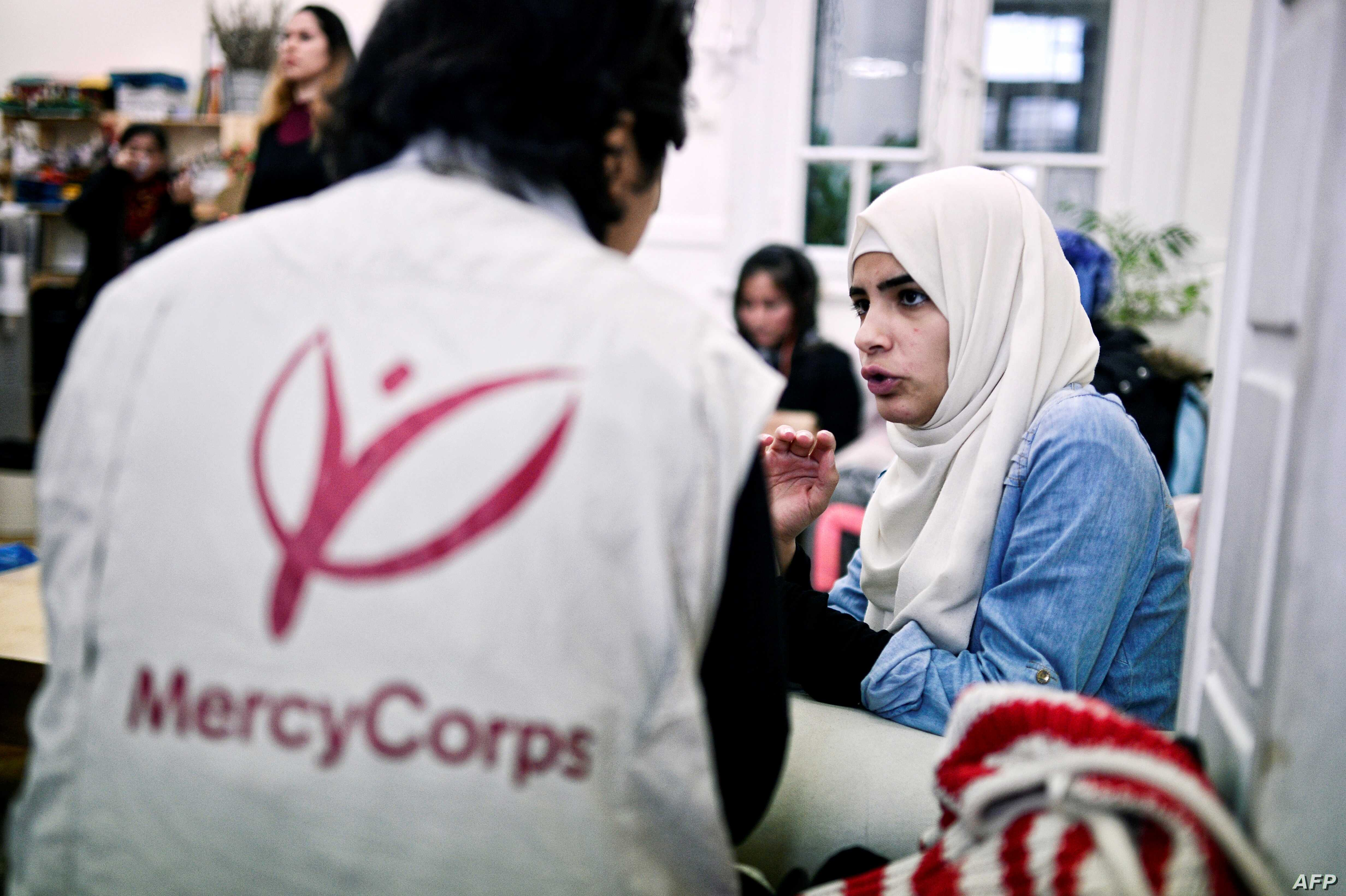 Iman Al Bohtori, right, a  Damascus University graduate, talks with a Mercy Corps translator at the 'Melissa' center for migrant women offering various classes and workshops to refugee women in Athens on March 10, 2017.