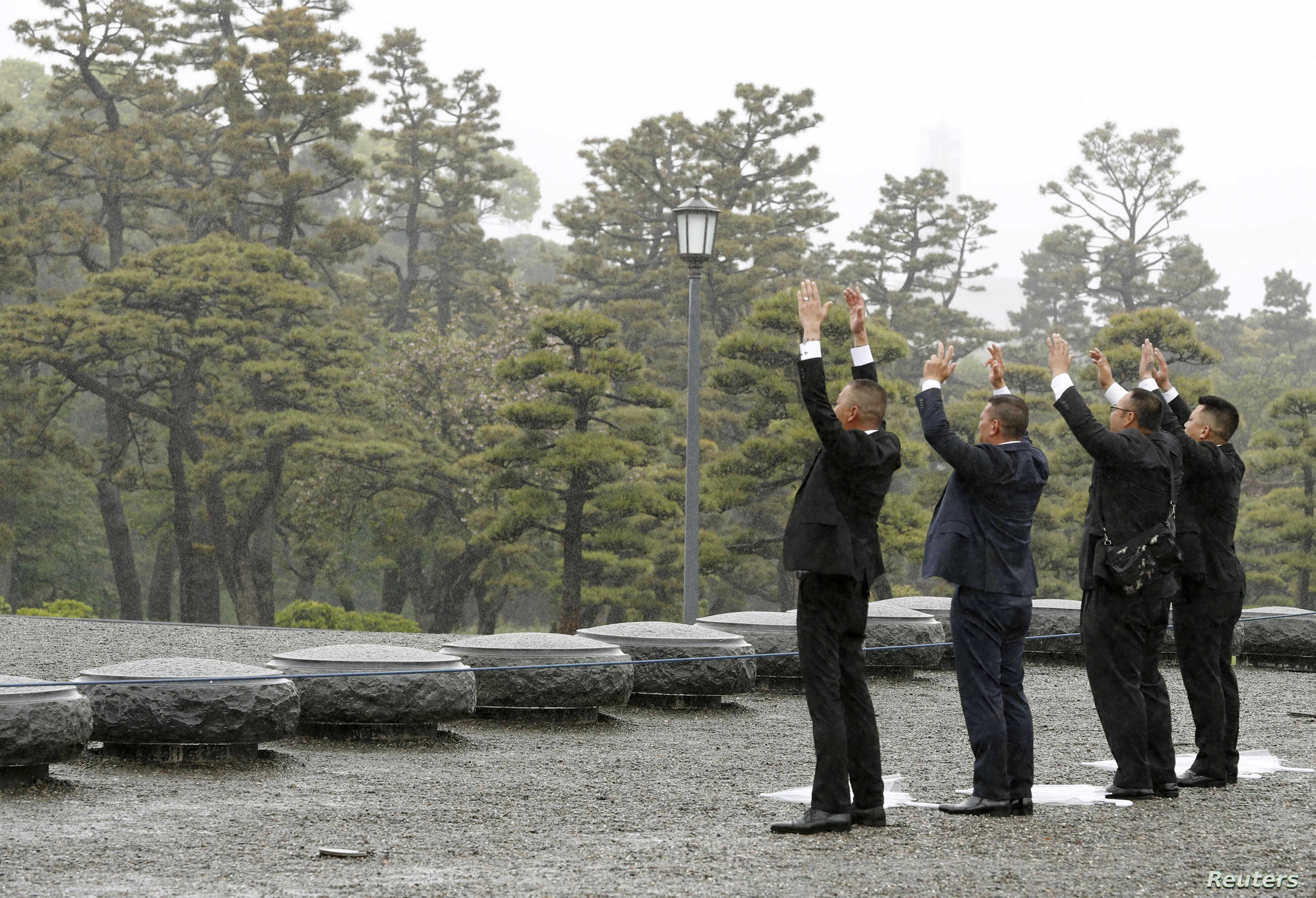 People raise hands as they shout 'banzai', or cheers, facing the Imperial Palace on the day of the Emperor Akihito's abdication in Tokyo, April 30, 2019.