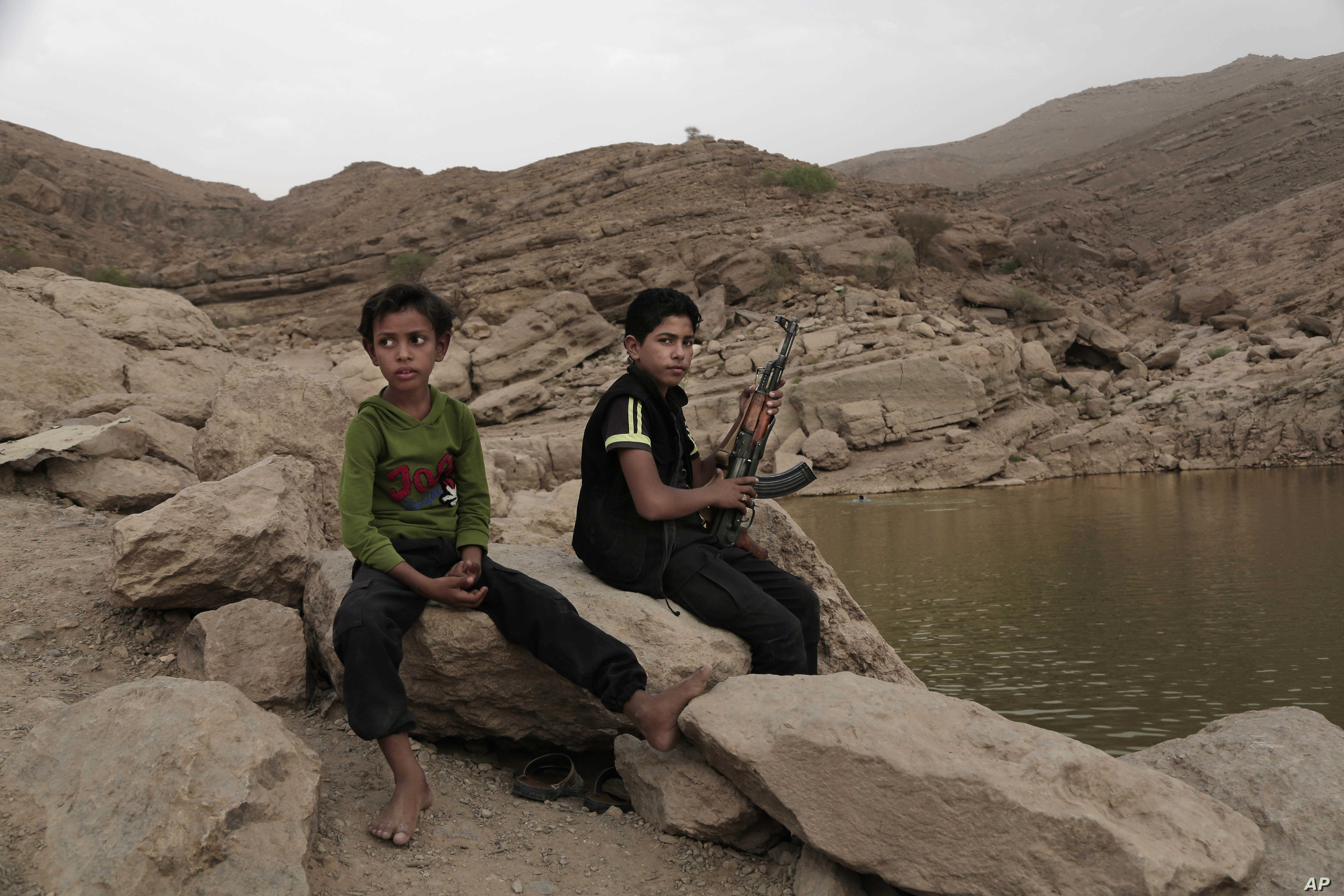 """In this July 30, 2018, photo, a 17 year-old boy holds his weapon in High dam in Marib, Yemen. Experts say child soldiers are """"the firewood"""" in the inferno of Yemen's civil war, trained to fight, kill and die on the front lines. (AP Photo/Narima..."""