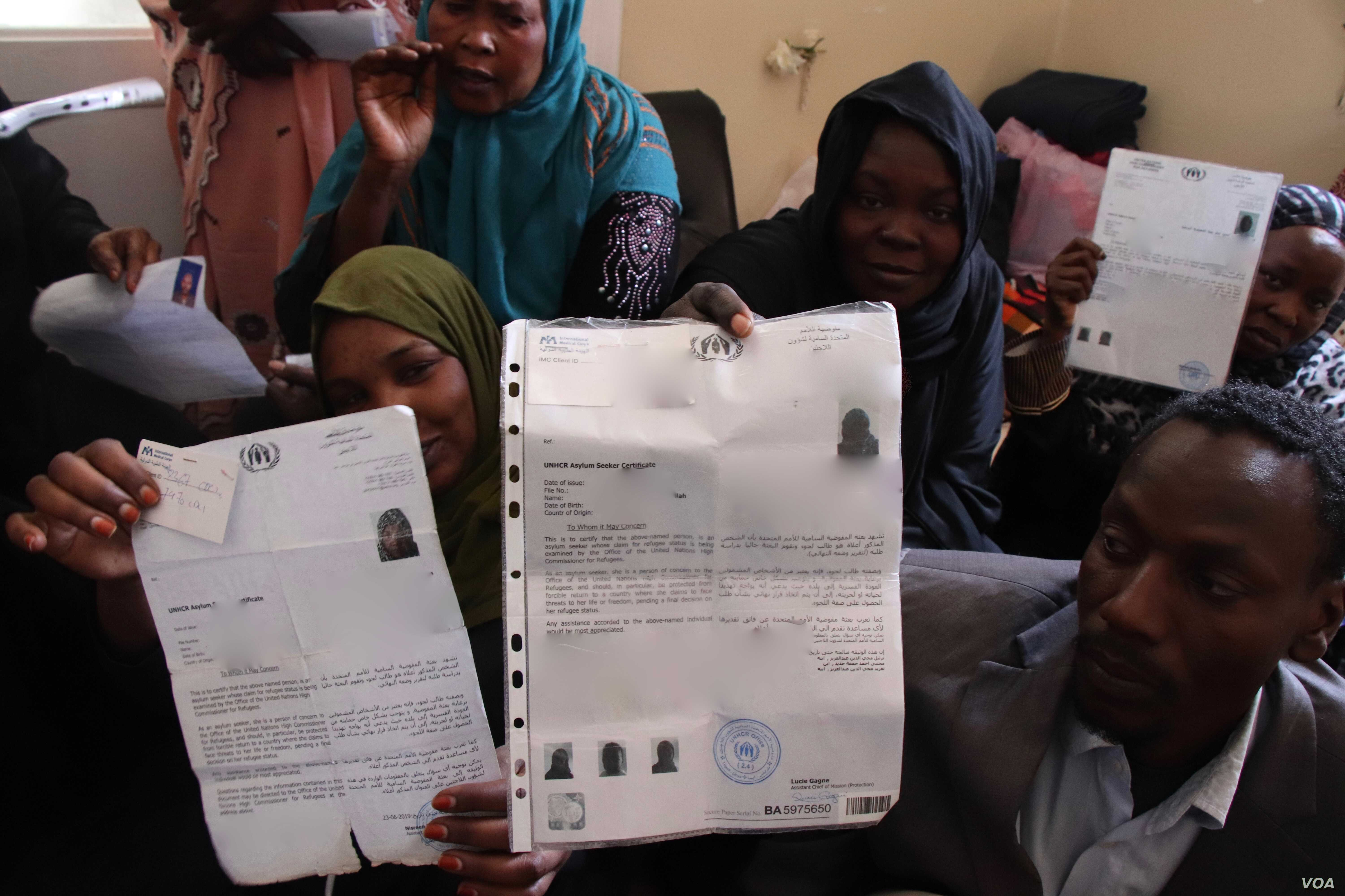 Asylum seekers from Sudan in Libya hold up documents from the United Nations, insisting that they have the right to flee their country, April 29, 2019. (H.Murdock/VOA)