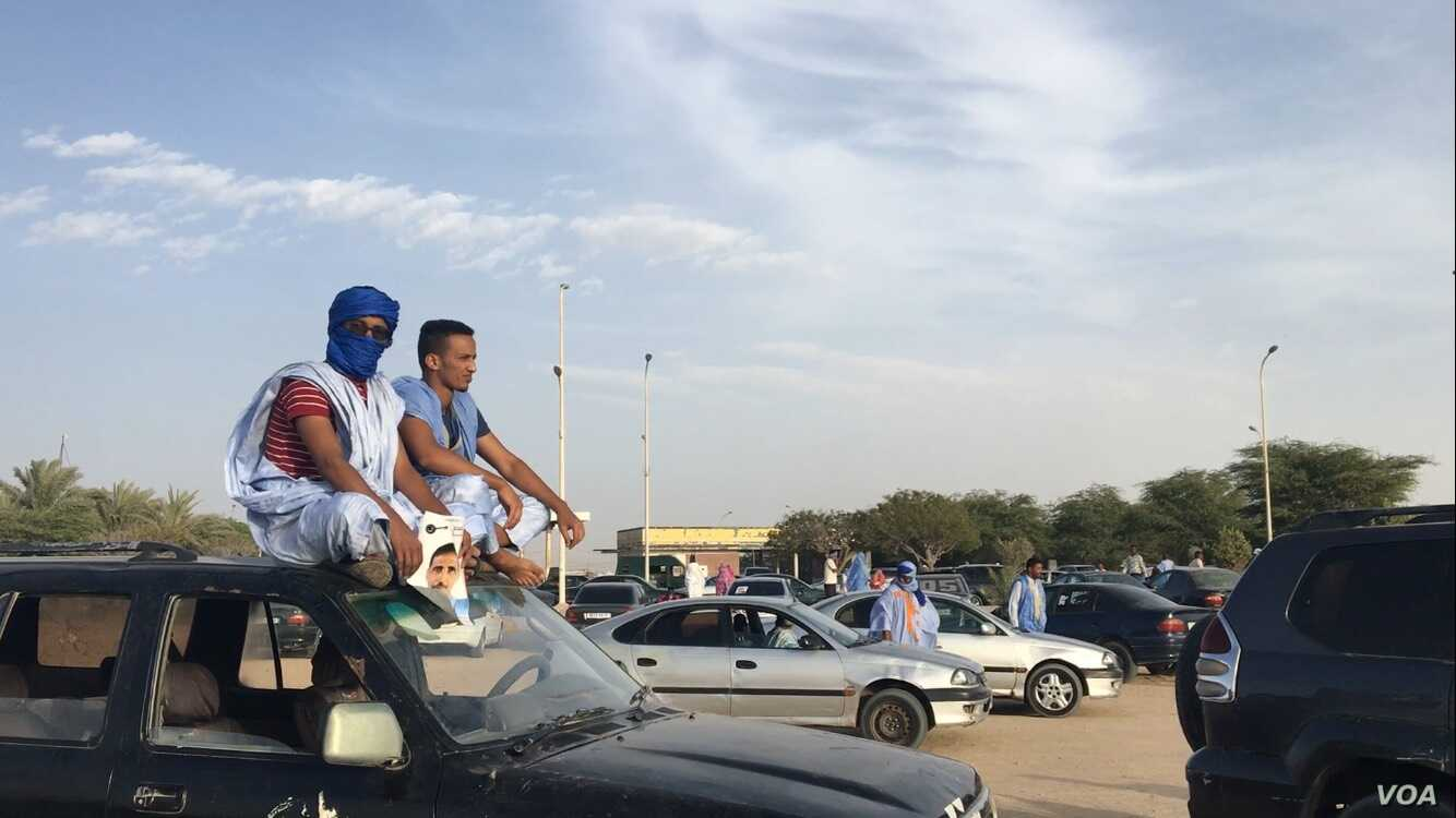 Supporters of opposition candidate Mohamed Ould Mouloud sit on their car for a better view of his final campaign rally. (Photo: E. Sarai)