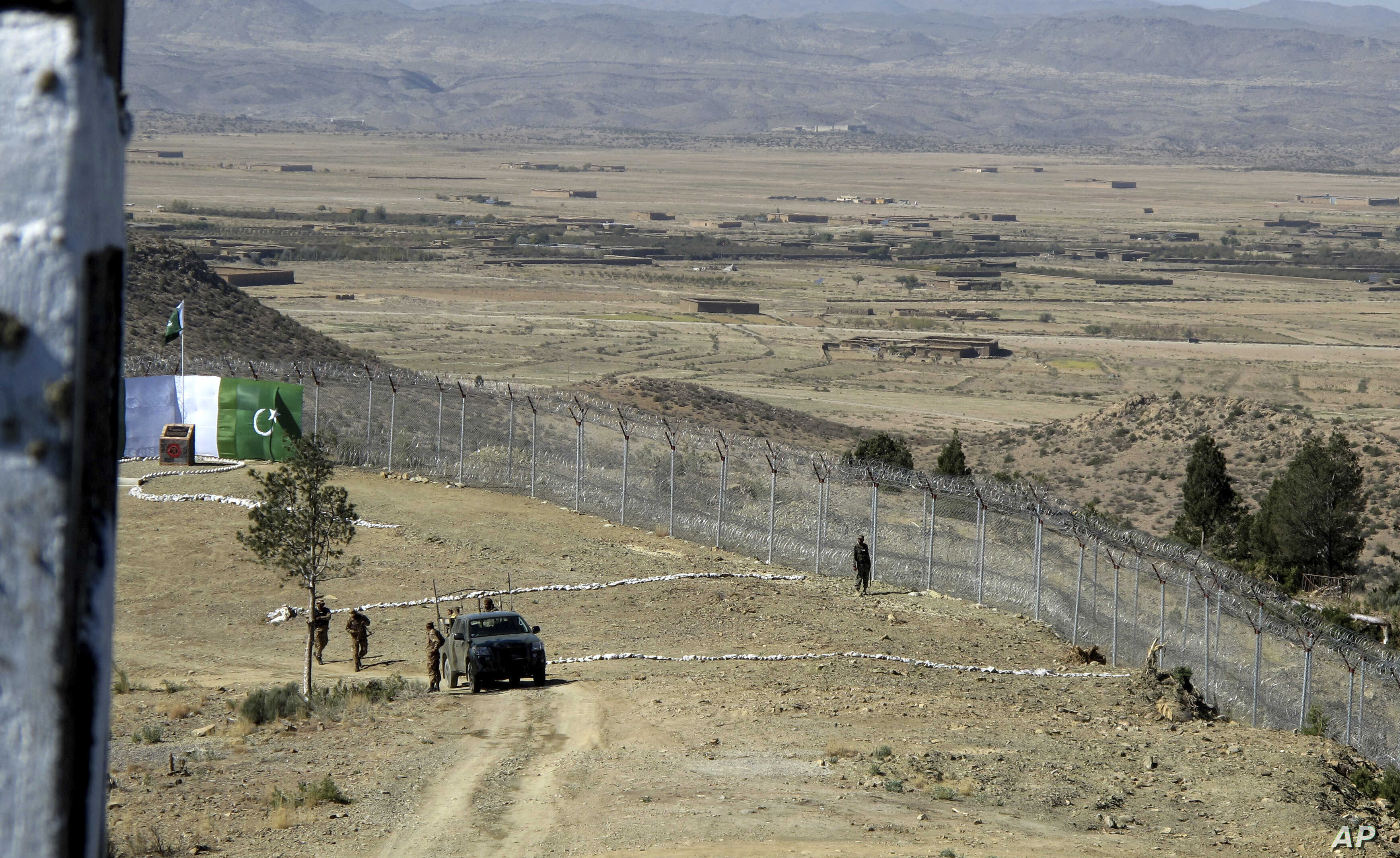 FILE - Pakistani soldiers stand guard at a newly erected fence between Pakistan and Afghanistan at Angore Adda, Pakistan, Oct. 18, 2017.