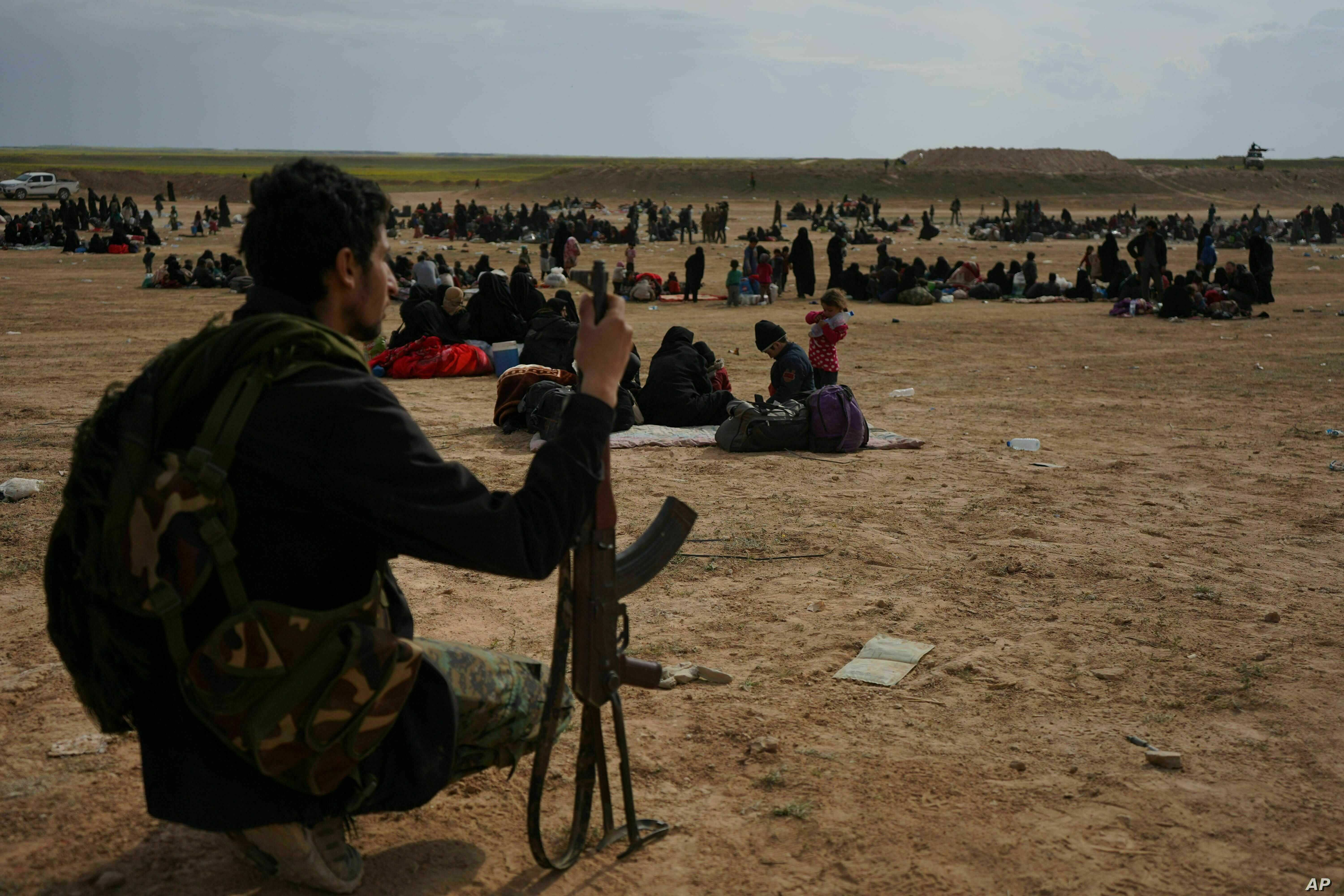 FILE -- A member of U.S.-backed Syrian Democratic Forces (SDF) watches over people who were evacuated out of the last territory held by Islamic State militants, outside Baghouz, Syria, March 5, 2019.