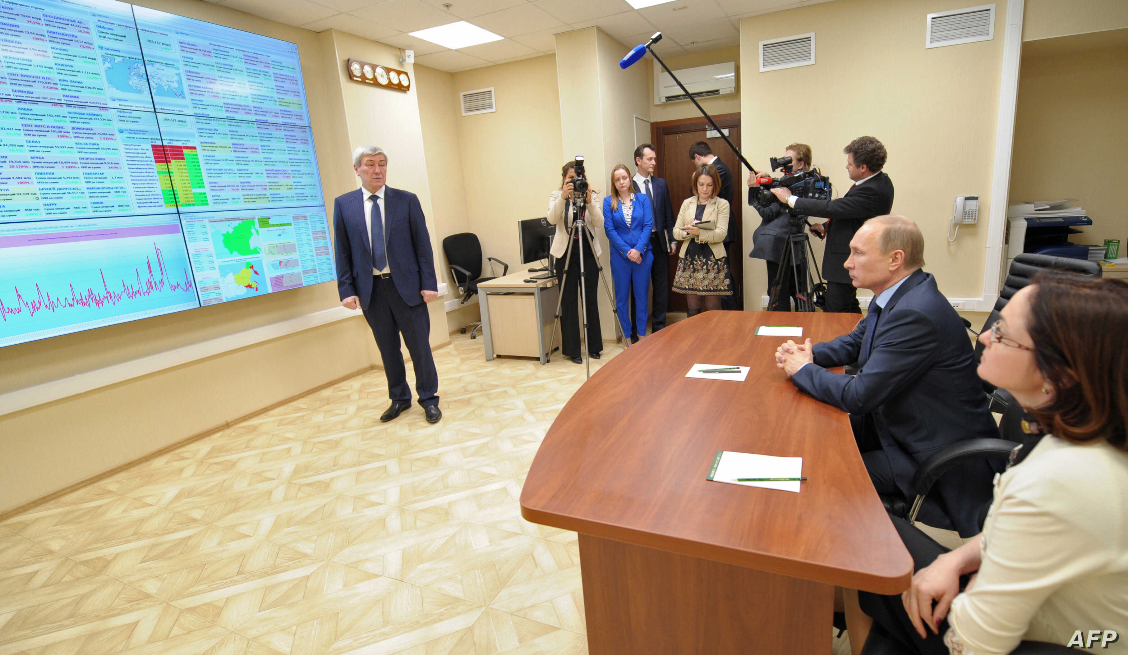 FILE - Russian President Vladimir Putin, 2nd right, visits the center for the assessment of risks of money laundering and terrorist financing, Rosfinmonitoring, in Moscow, March 4, 2014.