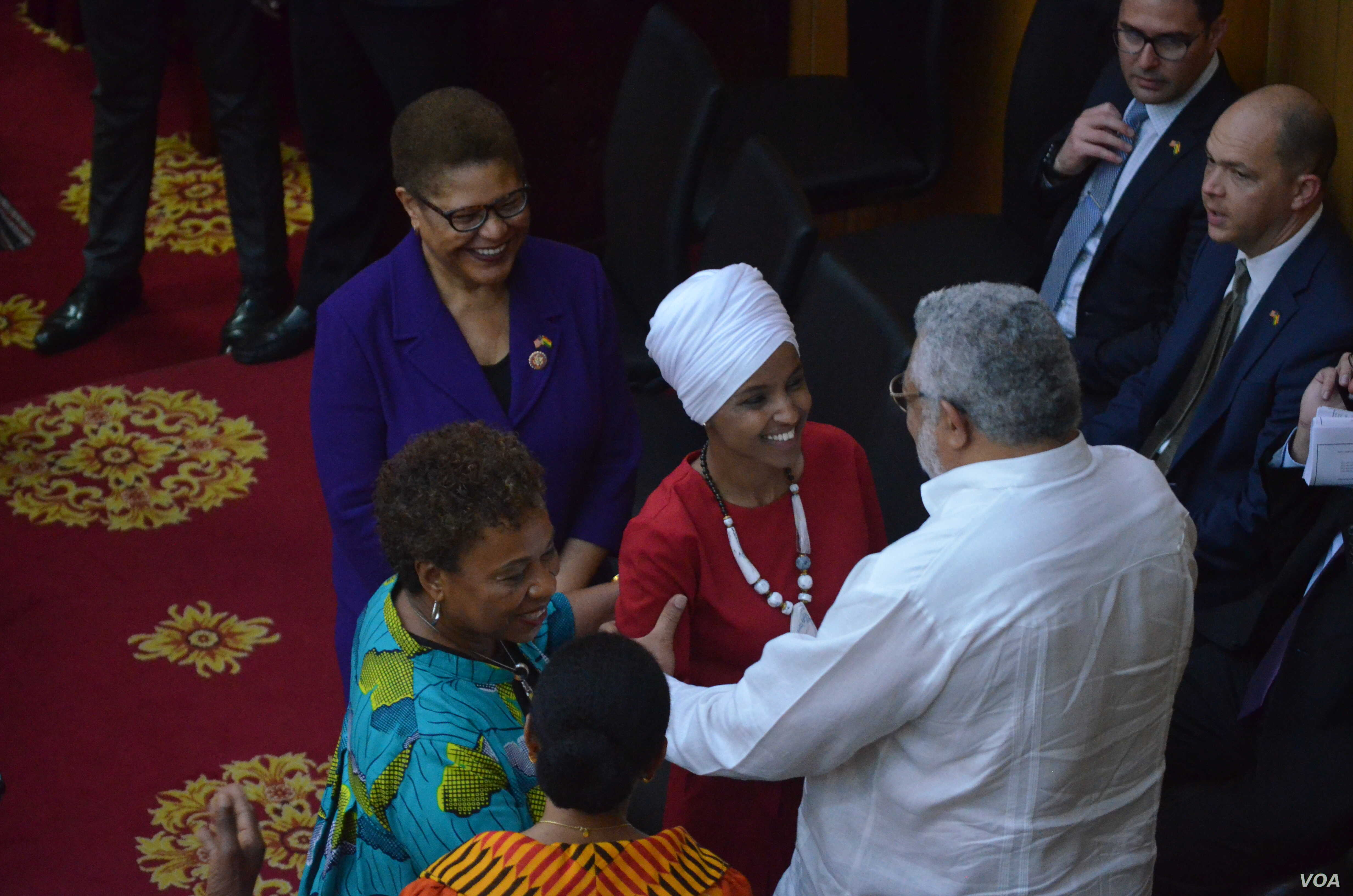 U.S. Representative Ilhan Omar is embraced by Ghana's former president, Jerry John Rawlings, at Ghana's parliament, July 31, 2019. (S. Knott/VOA)