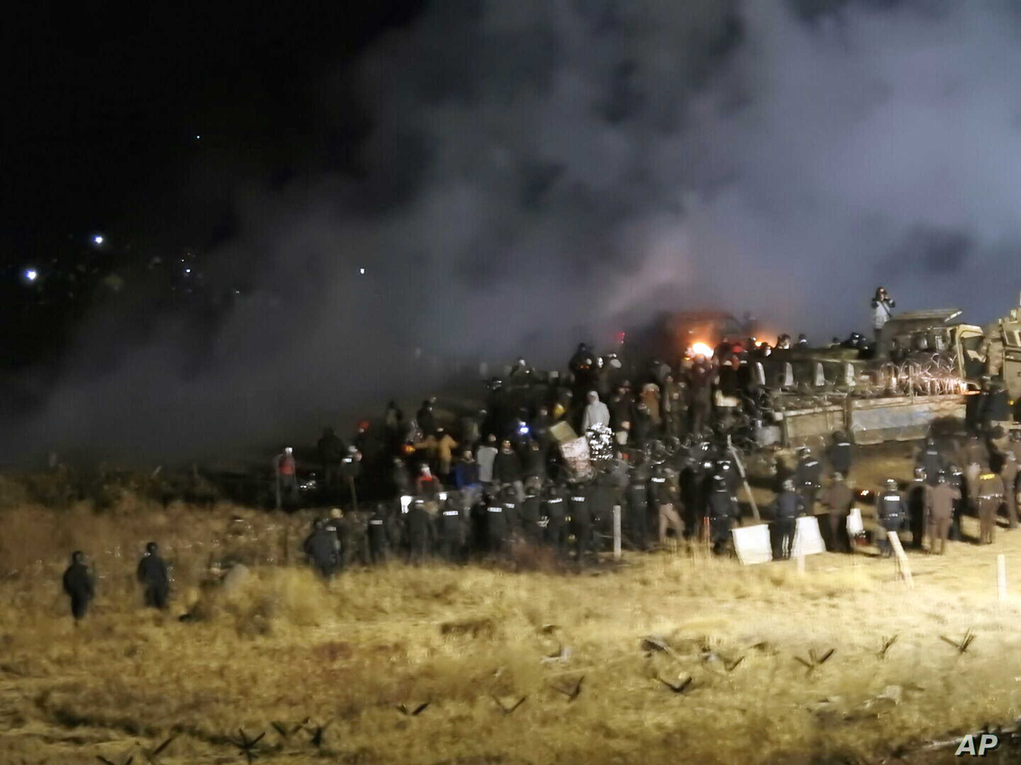 FILE - In this Nov. 20, 2016 file photo, provided by Morton County Sheriff's Department, law enforcement and protesters clash near the site of the Dakota Access pipeline in Cannon Ball, N.D.
