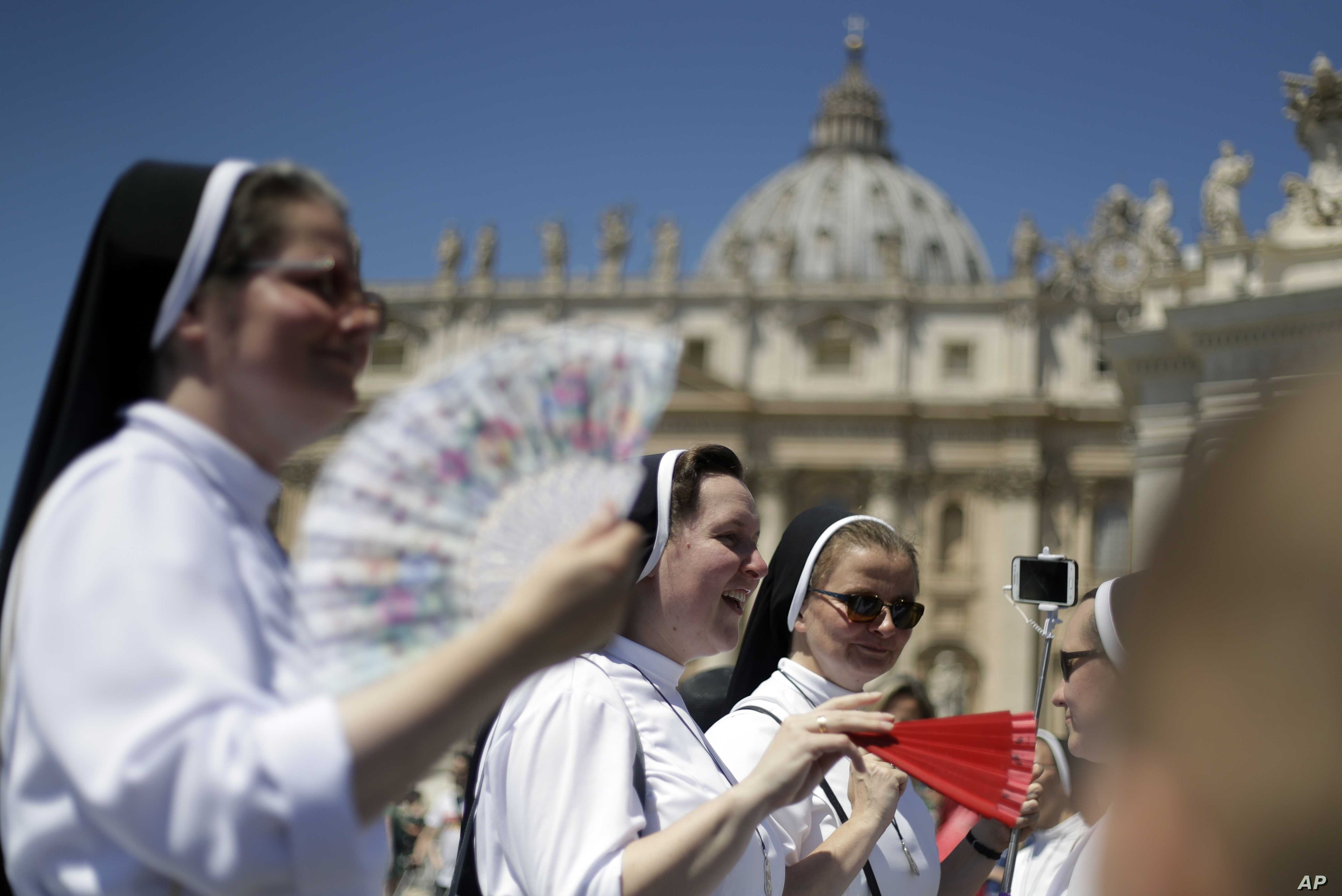 Nuns use fans to cool-off in St. Peter's Square at the Vatican, June 30, 2019.