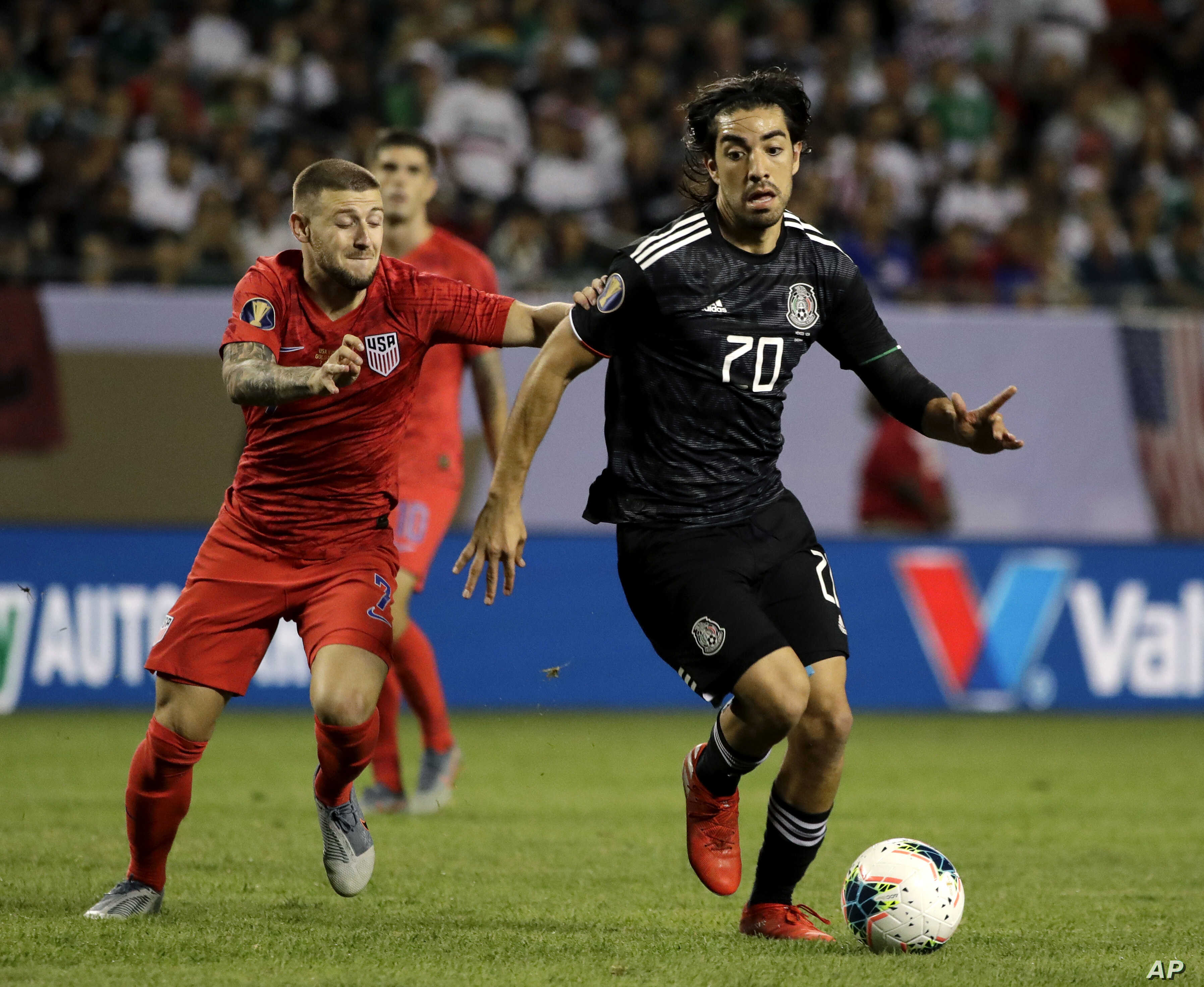Mexico forward Rodolfo Pizarro, right, controls the ball against United States forward Paul Arriola during the second half of th