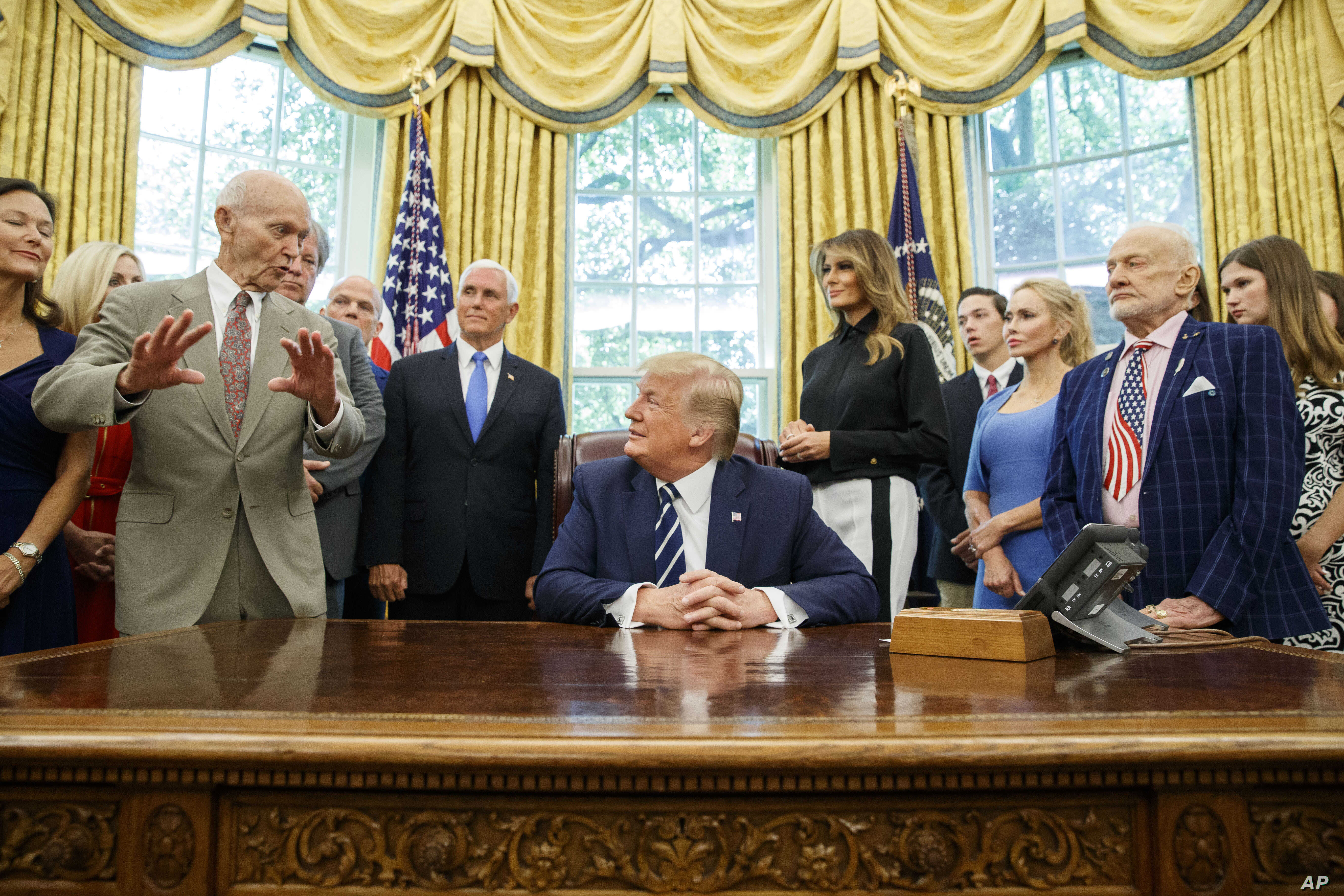 President Donald Trump, accompanied by Apollo 11 astronauts Michael Collins, left, and Buzz Aldrin, with Vice President Mike Pence and first lady Melania Trump, listens during photo opportunity commemorating 50th anniversary of Apollo 11 moon landing