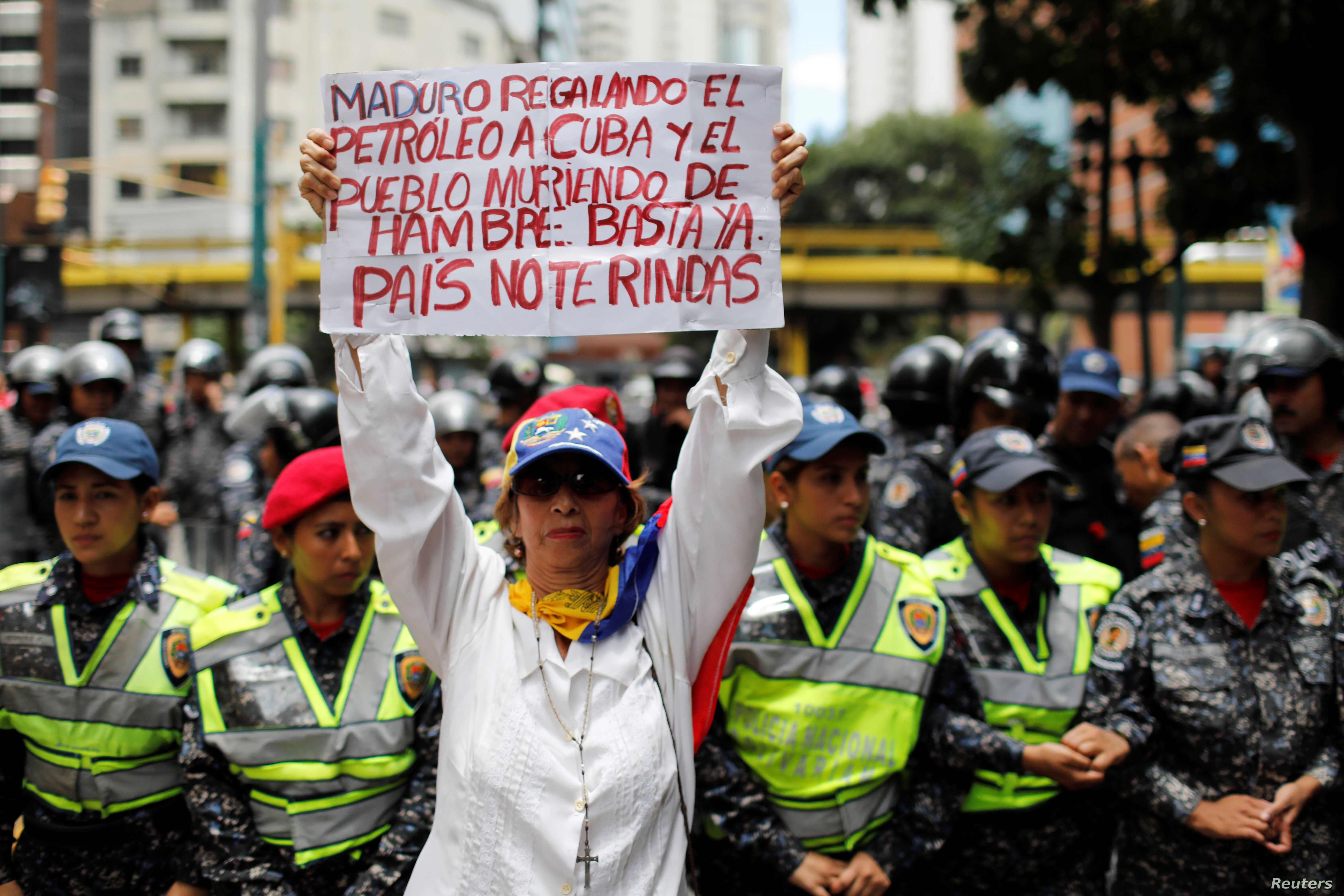 "FILE - A woman holds a sign that reads: ""Maduro gives oil to Cuba and people die of hunger. Enough. Country do not give up"" during a protest in Caracas, Venezuela, Aug. 16, 2018."