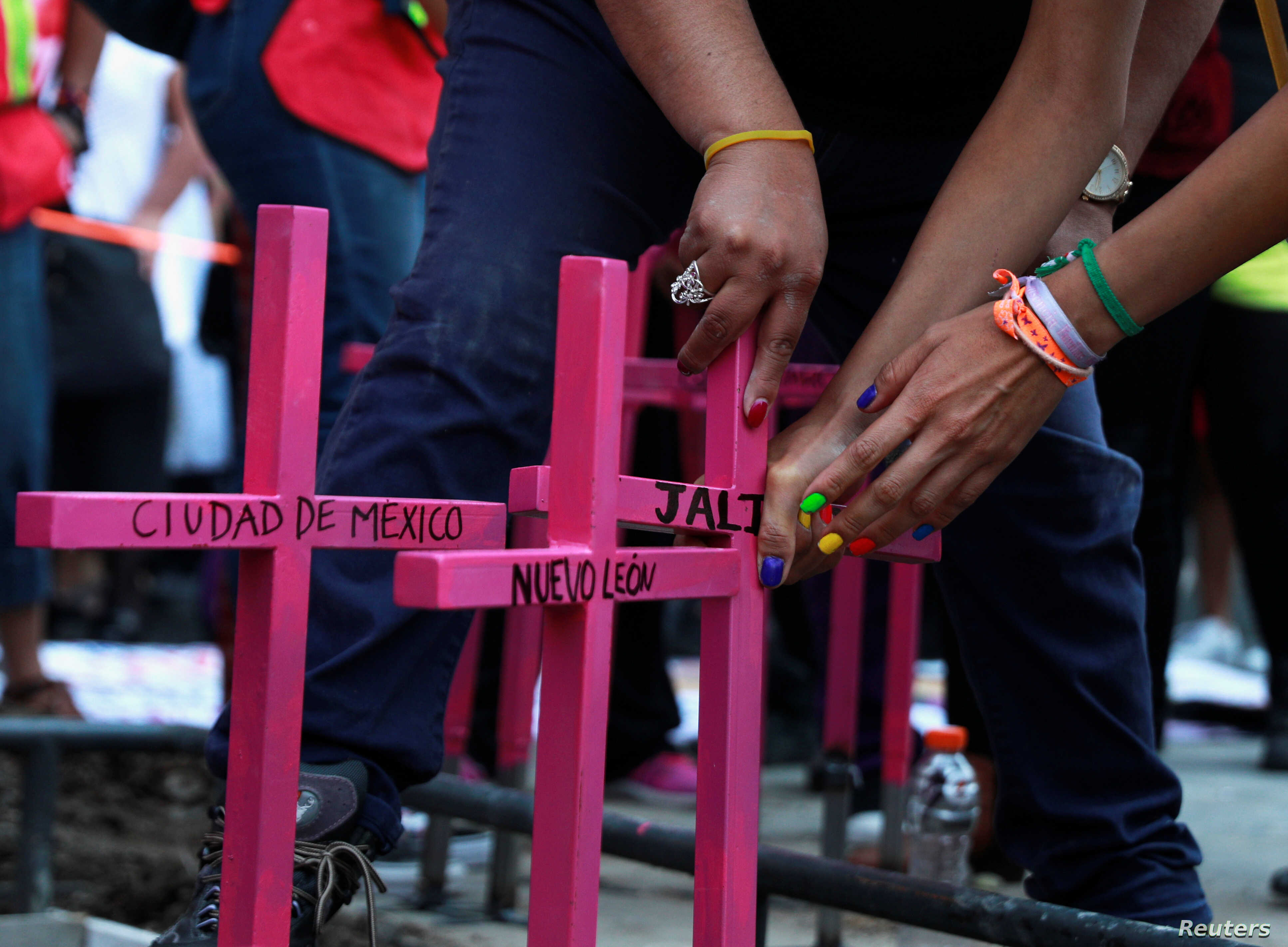 Women place pink crosses at a makeshift monument against femicide with names of the states of Mexico, during a protest against femicide and violence against women, in Mexico City, March 24, 2019.