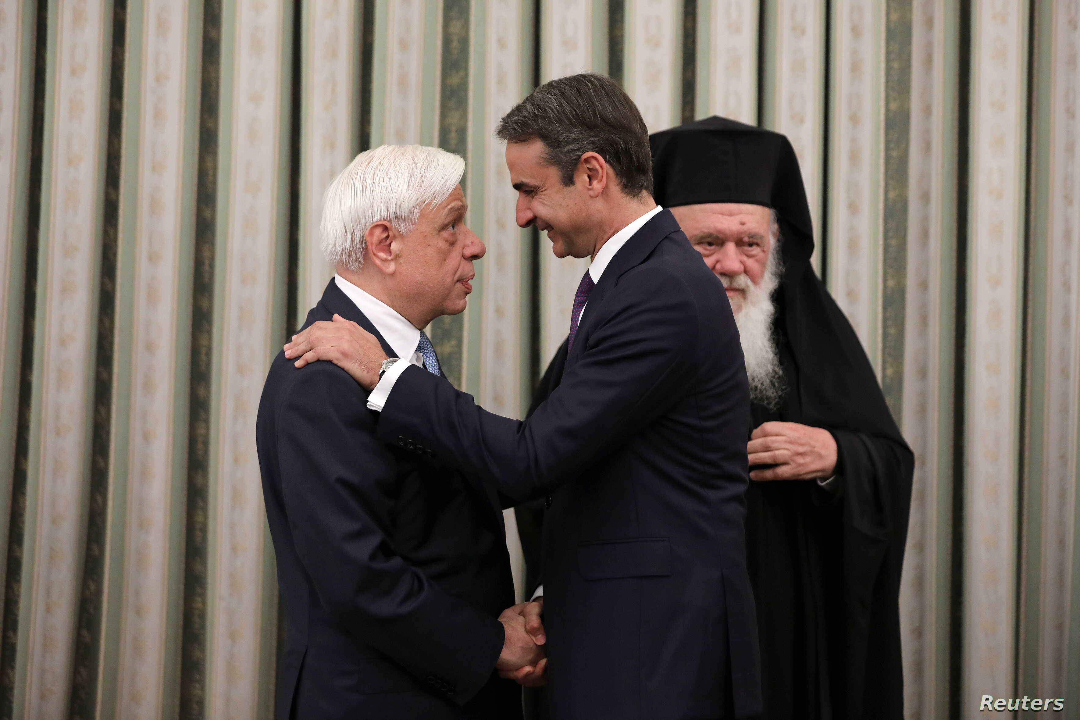 New Democracy conservative party leader Kyriakos Mitsotakis shakes hands with Greek President Prokopis Pavlopoulos, near Greece's Orthodox Church Archbishop Ieronimos, at a swearing-in ceremony as prime minister, in Athens, Greece, July 8, 2019.