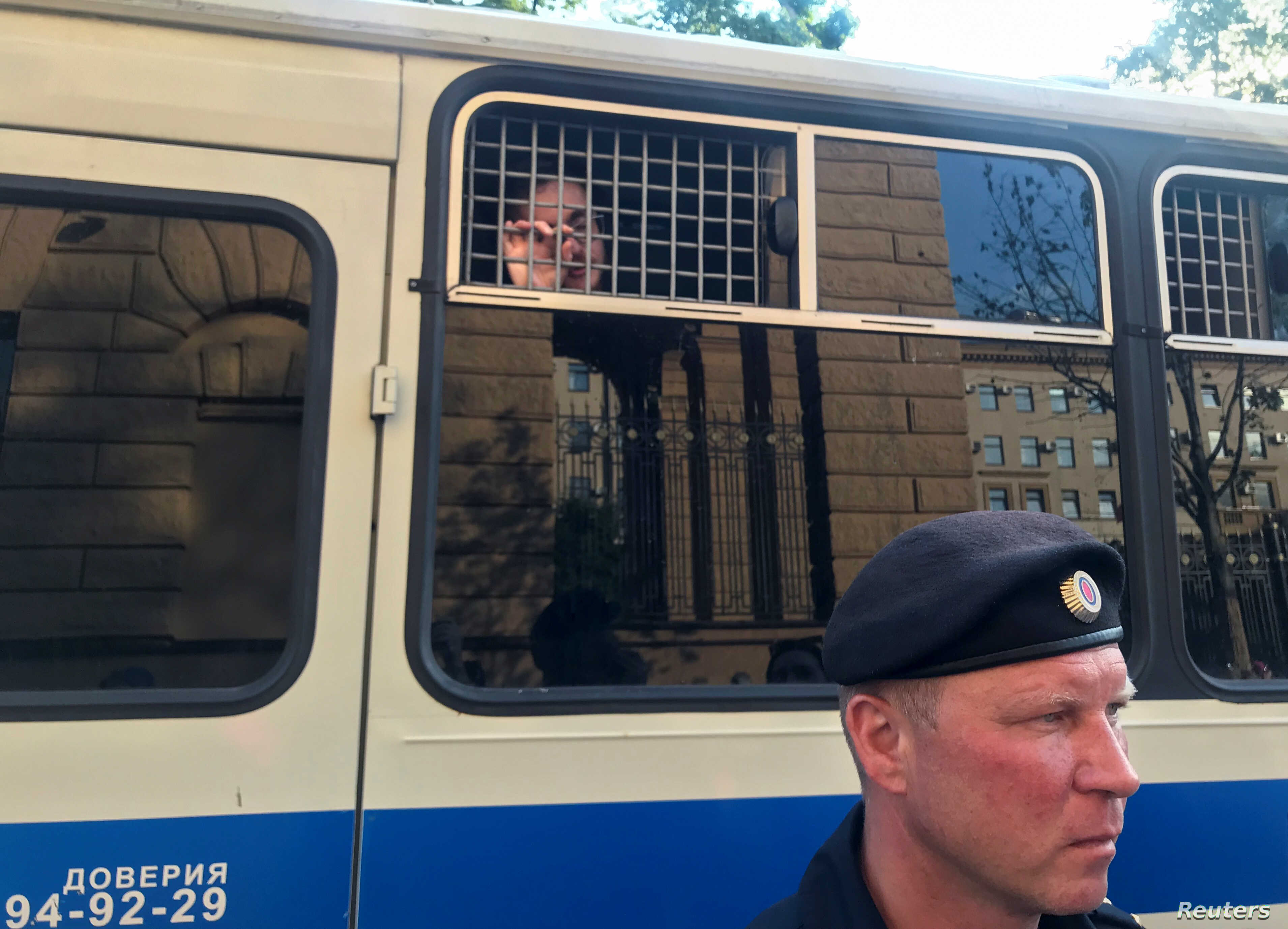 FILE - A police officer stands in front of a bus with reporters detained after a rally in Moscow, Russia, June 7, 2019.