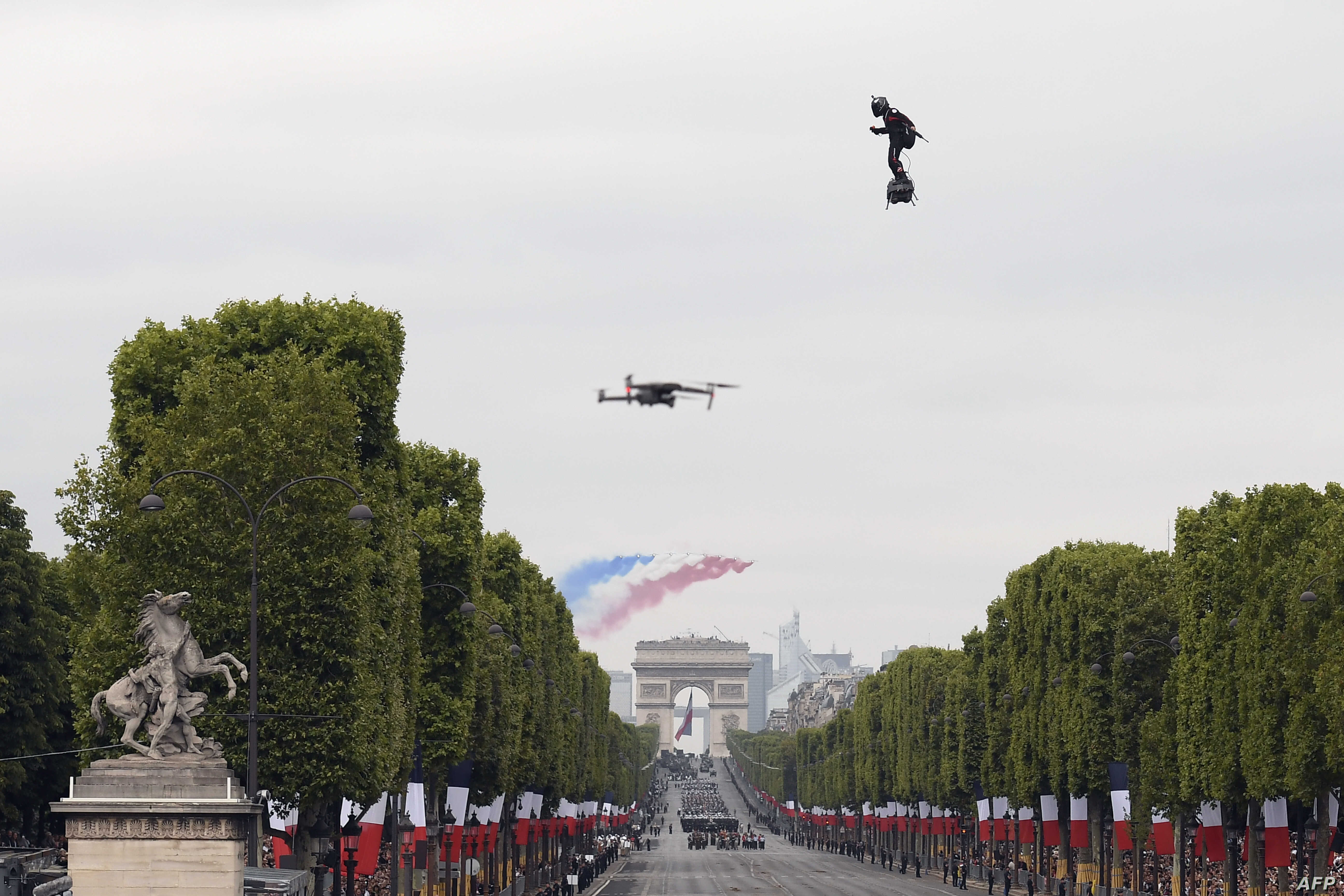 """Zapata CEO Franky Zapata flies a jet-powered hoverboard or """"Flyboard"""" during the Bastille Day military parade down the Champs-Elysees avenue in Paris, France, July 14, 2019."""