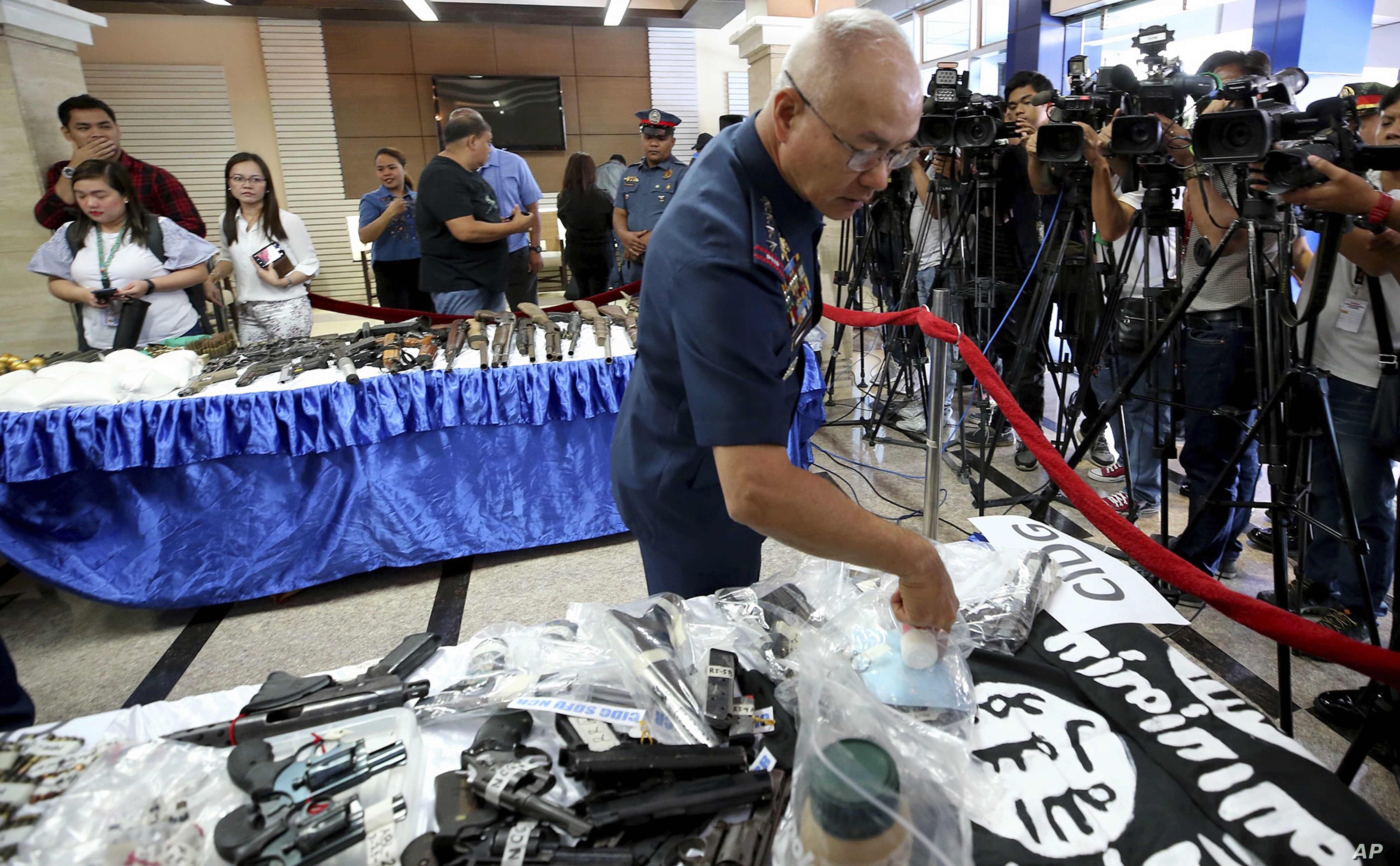Philippine National Police Chief Gen. Oscar Albayalde inspects guns, explosives, and Islamic State group-style black flags during a news conference, at Camp Crame in suburban Quezon city northeast of Manila, Philippines, April 1, 2019.