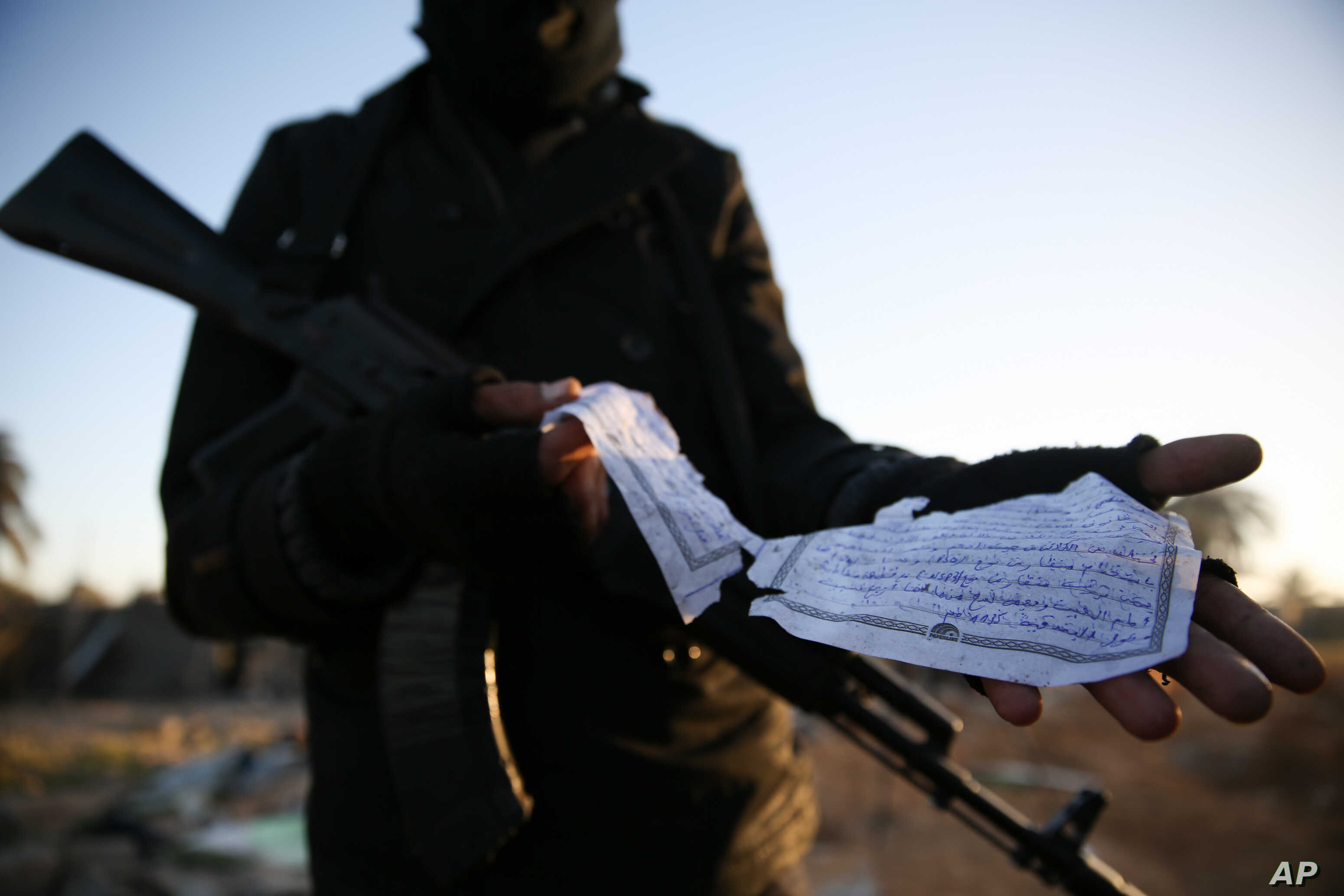 A member of the Libyan security forces displays part of a document in Arabic describing weaponry that was found at the site of U.S. airstrikes on an Islamic State camp near the western city of Sabratha, Libya, Feb. 20, 2016.