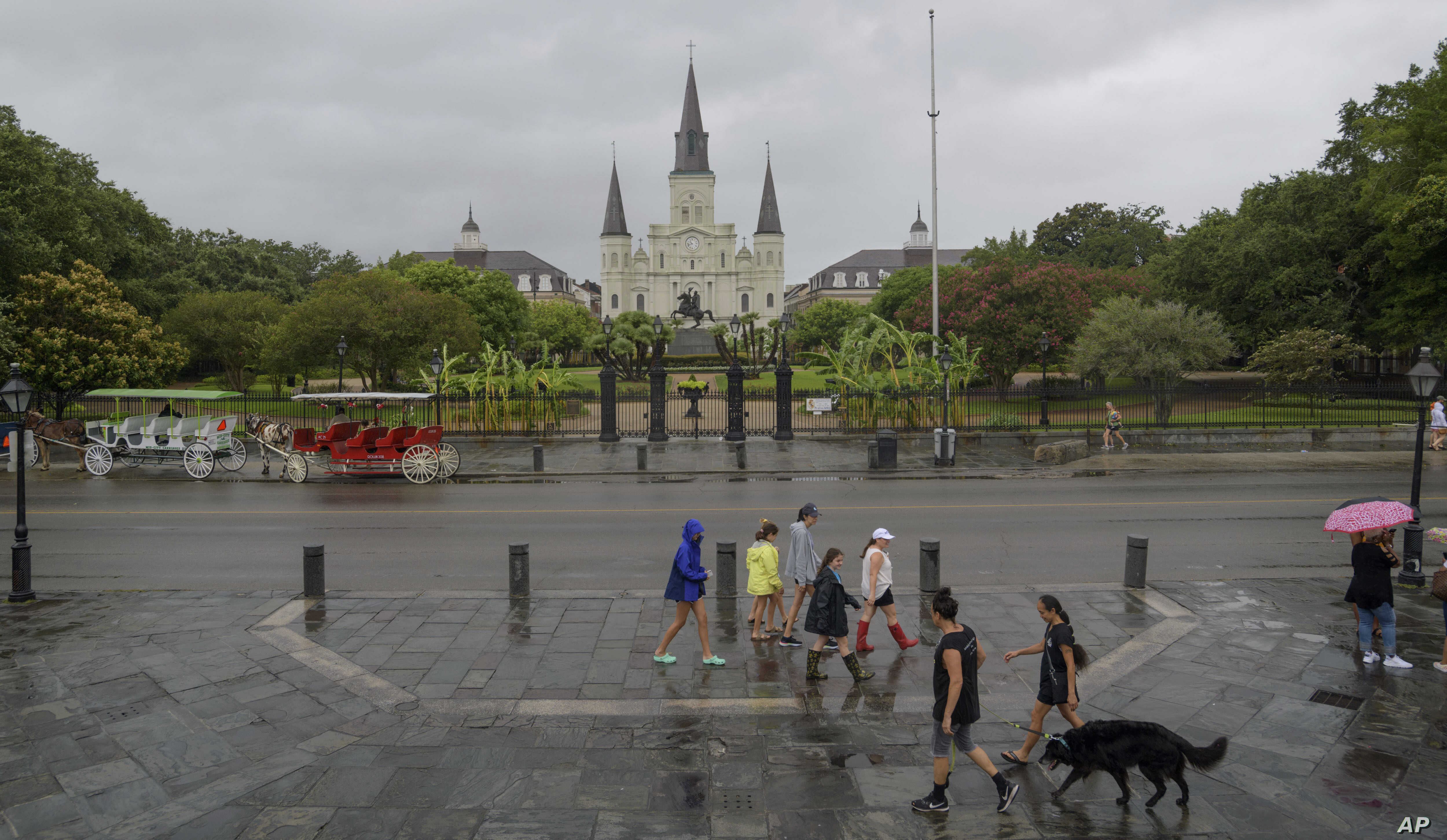 People walk past Jackson Square and St. Louis Cathedral in the French Quarter before landfall of Tropical Storm Barry from the Gulf of Mexico in New Orleans, La., July 12, 2019.