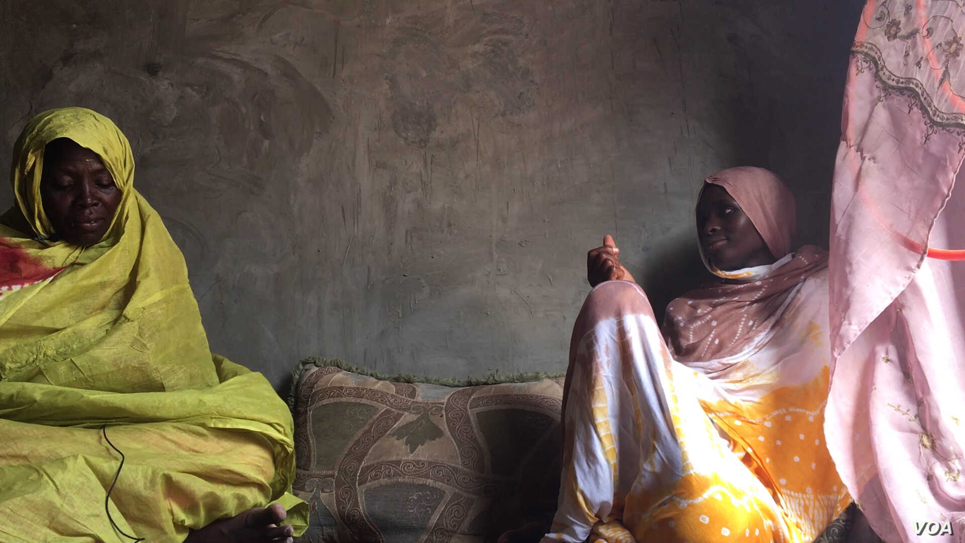 M'Barka Mint Yarba and her mother Oulmoulkhair sit on the floor of their still unfinished home in Mellah (E. Sarai/VOA)
