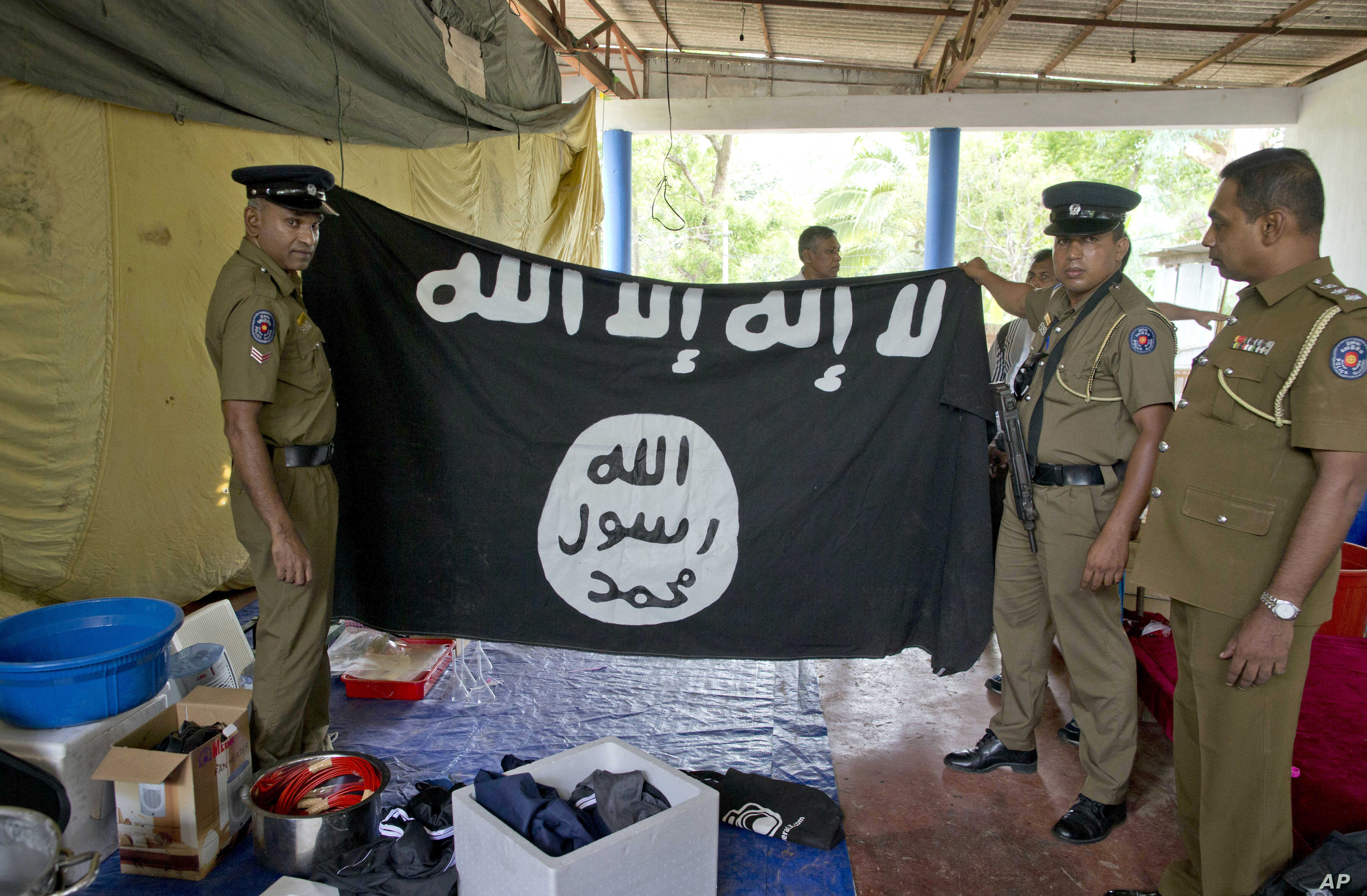 Police officers display an Islamic State flag recovered during a raid in Ampara, Sri Lanka, April 28, 2019.