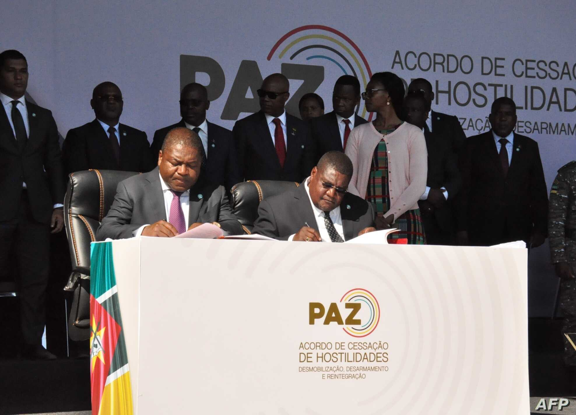 Mozambique's President Filipe Nyusi, left, and Renamo leader Ossufo Momade sign a cease-fire agreement in Gorongosa, in this handout photo taken and released by the office of the President of Mozambique on Aug. 1, 2019.