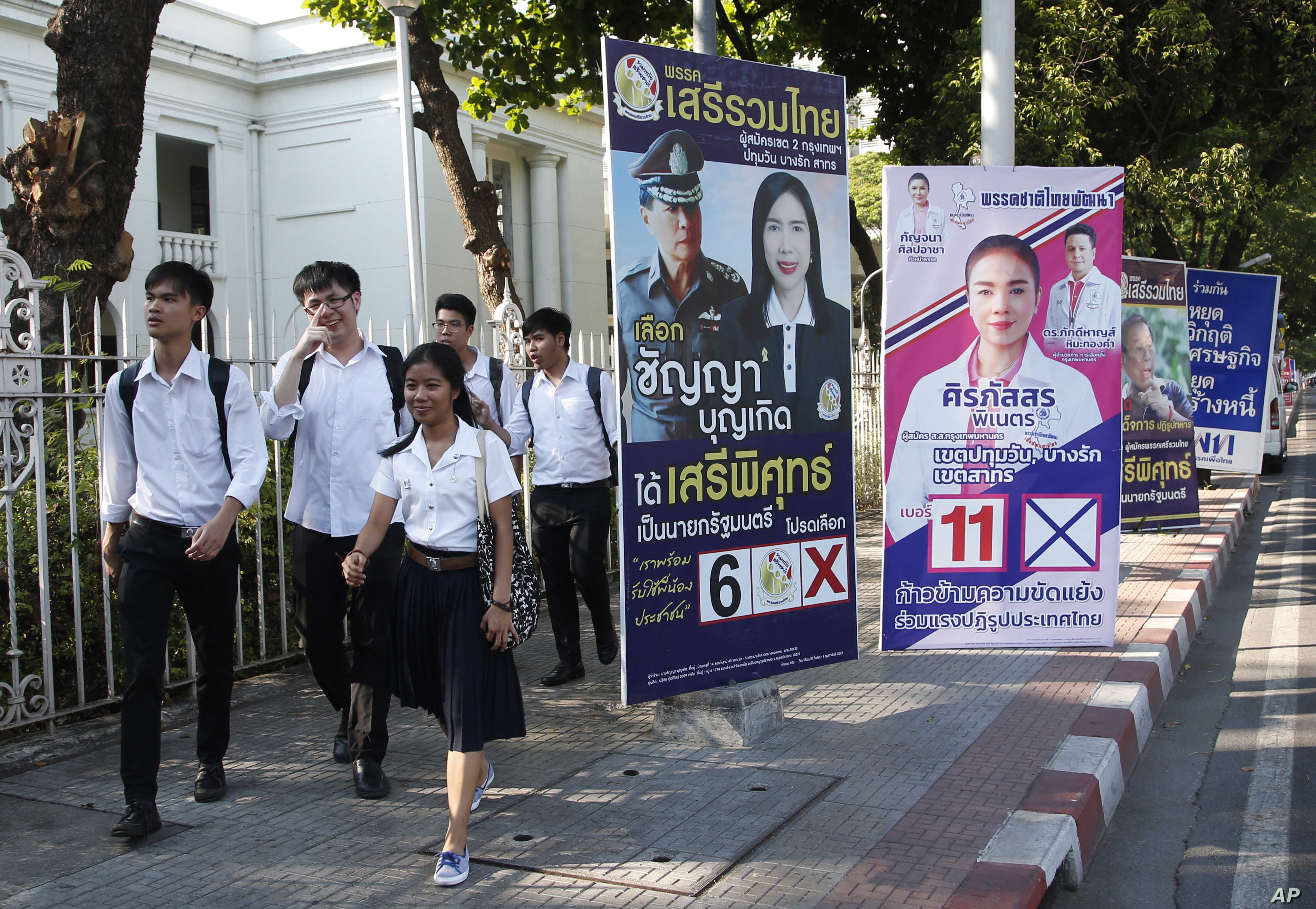 Students of Chulalongkorn University walks past election campaign posters in Bangkok, Thailand, March 12, 201.