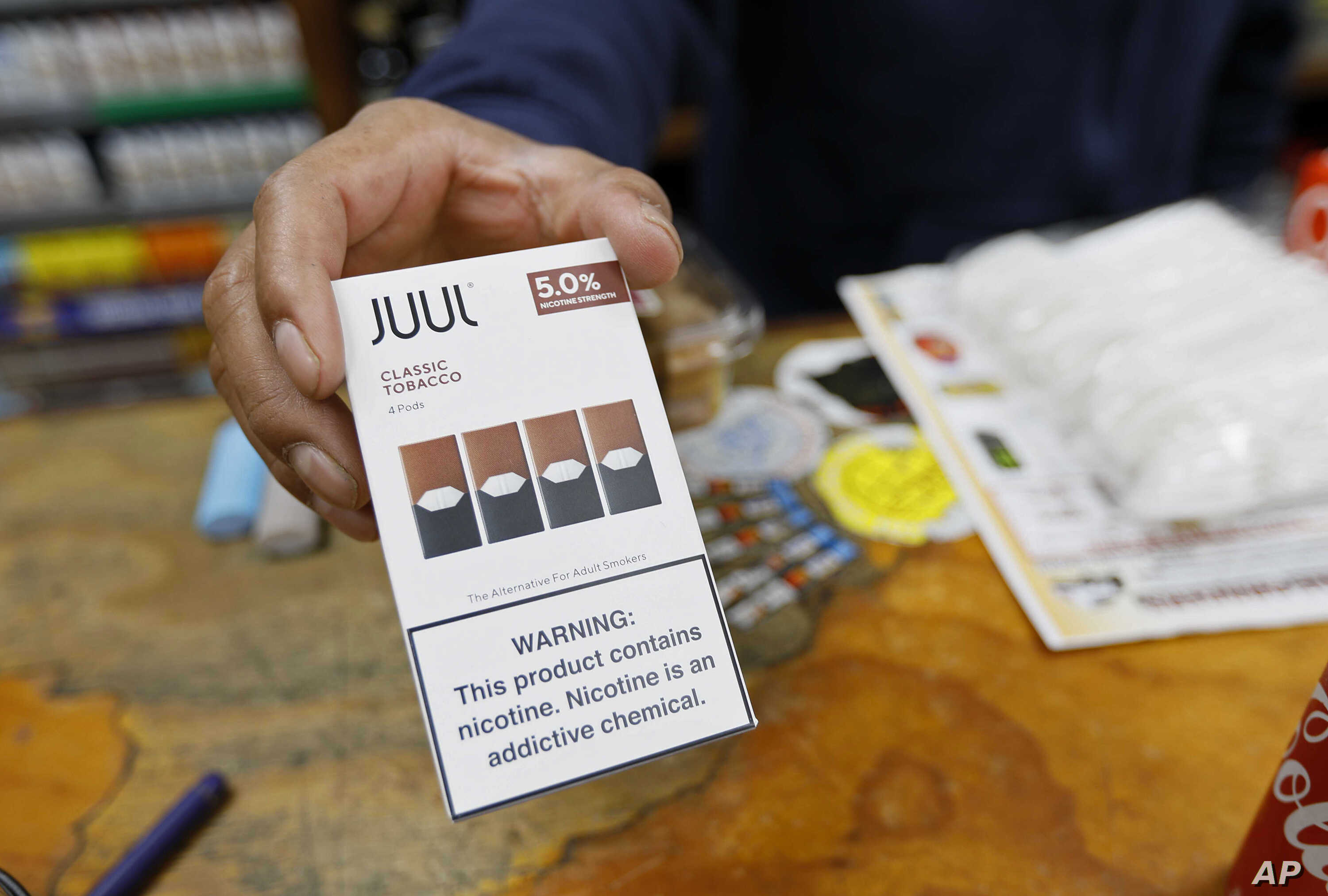 FILE - A cashier displays a packet of tobacco-flavored Juul pods at a store in San Francisco, June 17, 2019.