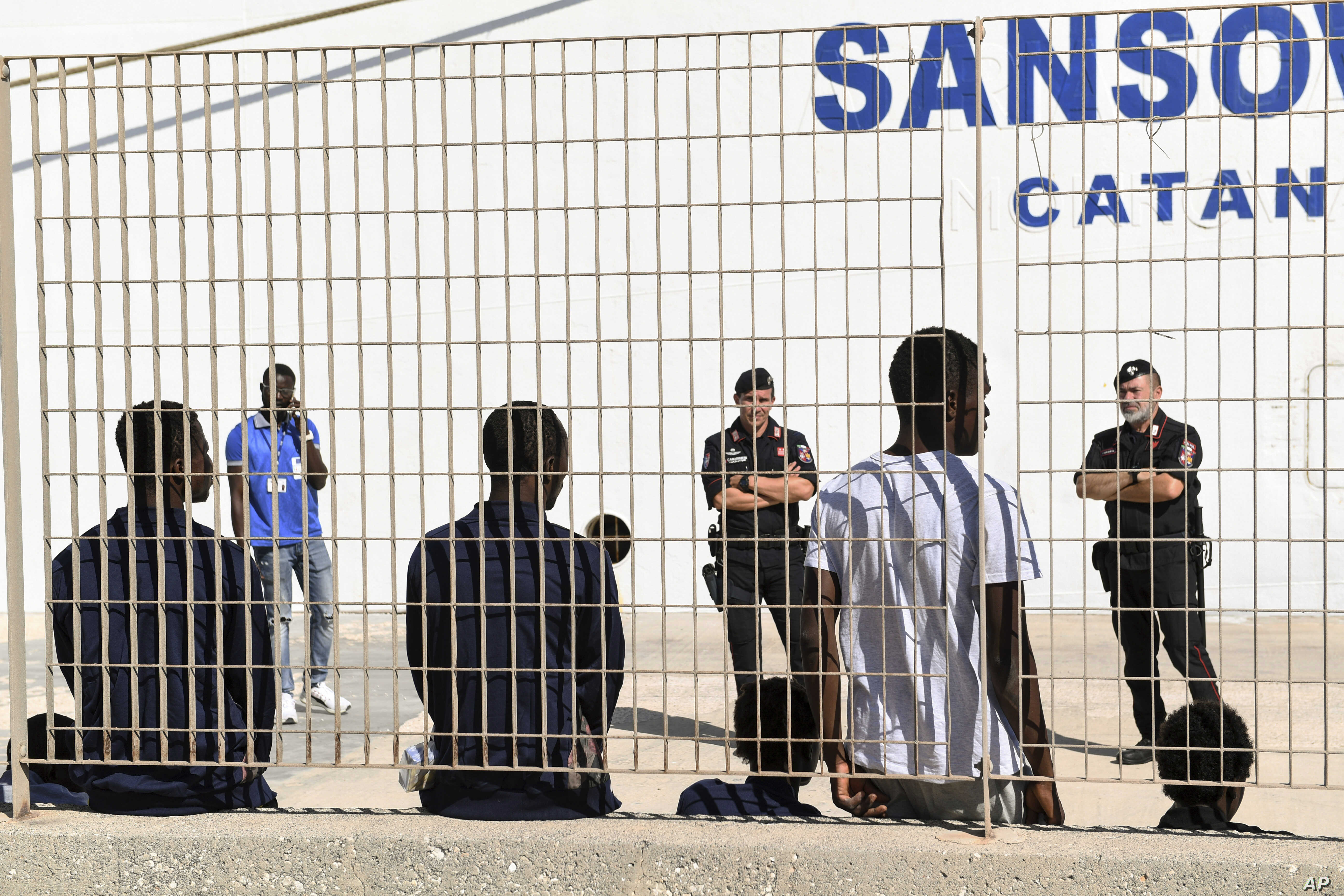 Some of migrant minors allowed to disembark the Open Arms vessel, anchored off the Sicilian vacation and fishing island of Lampedusa, southern Italy, wait to be taken to the Sicilian port of Porto Empedocle from Lampedusa, Aug. 19, 2019.