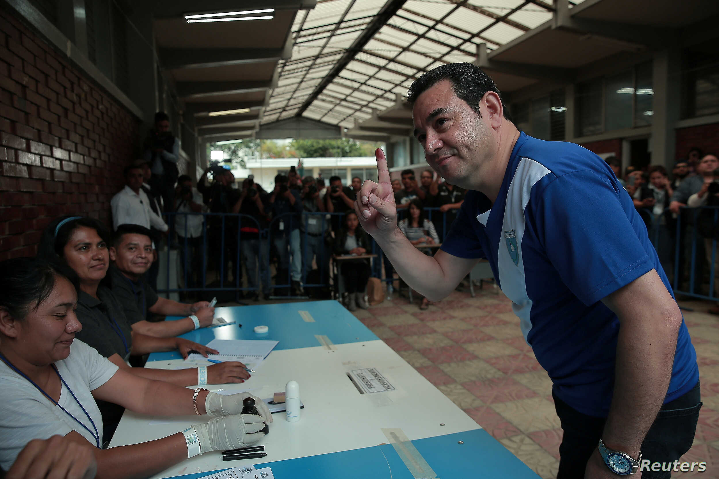 Guatemalan President Jimmy Morales shows his ink-stained finger after casting his ballot at a polling station during the presidential election second round run-off vote in Mixco, Guatemala, Aug. 11, 2019.