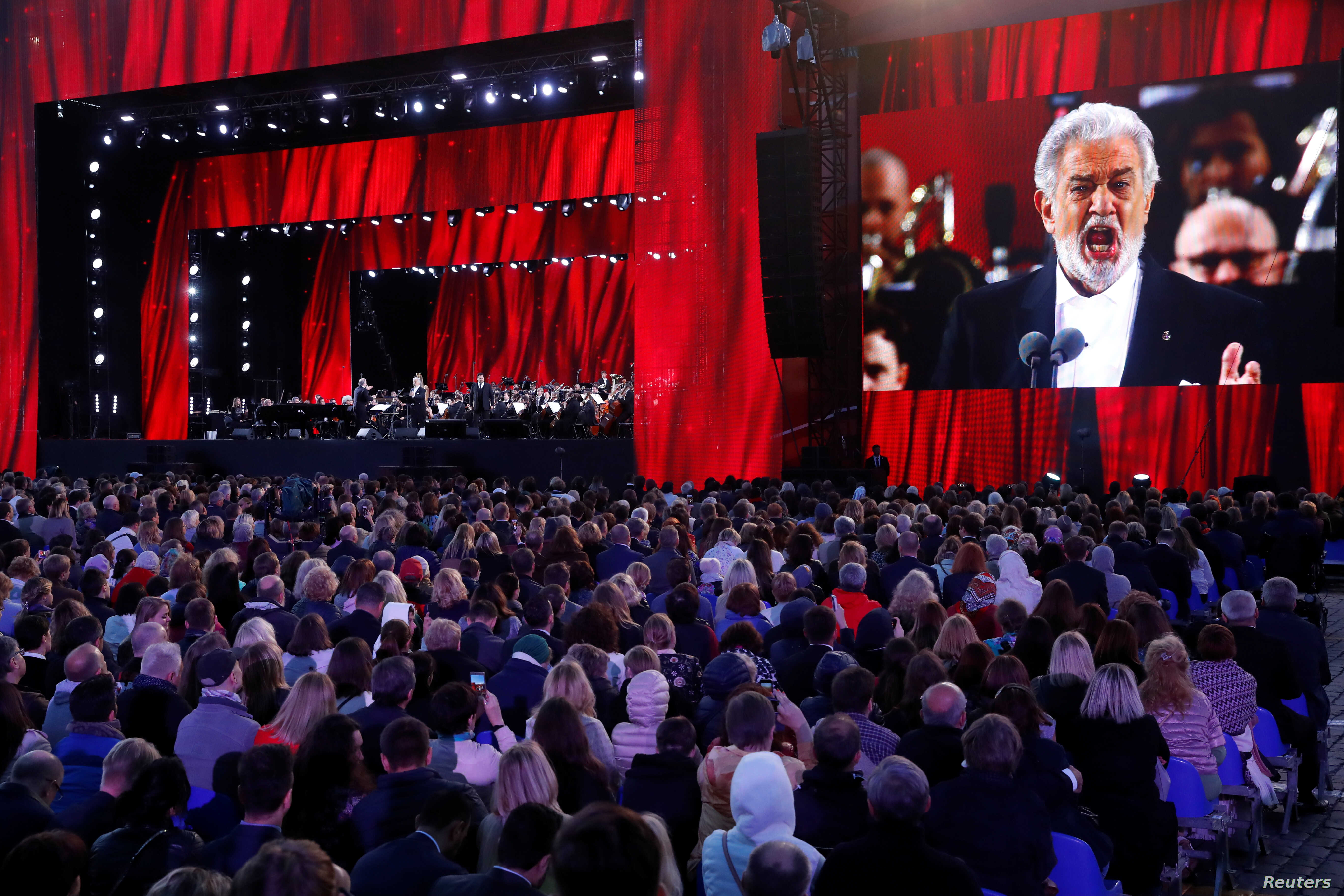 FILE - People listen to Spanish tenor Placido Domingo during a gala concert, dedicated to the upcoming World Cup, in Red Square in Moscow, Russia, June 13, 2018.