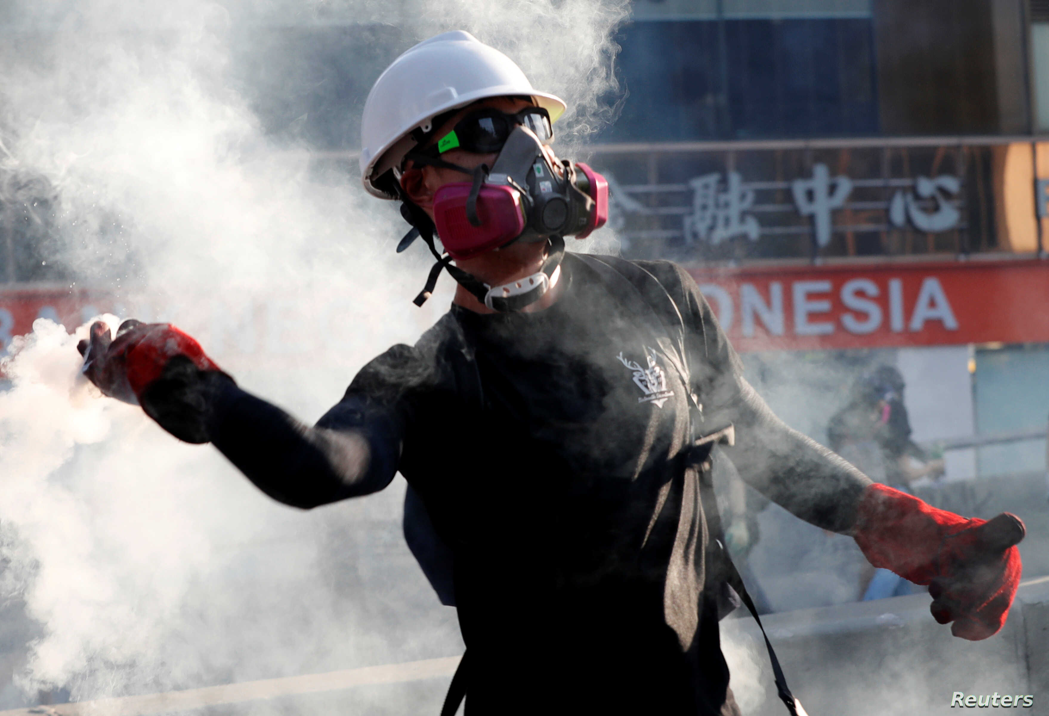 A protester throws a tear gas canister back at the police during a demonstration in support of the city-wide strike and to call for democratic reforms in Hong Kong, China, Aug. 5, 2019.