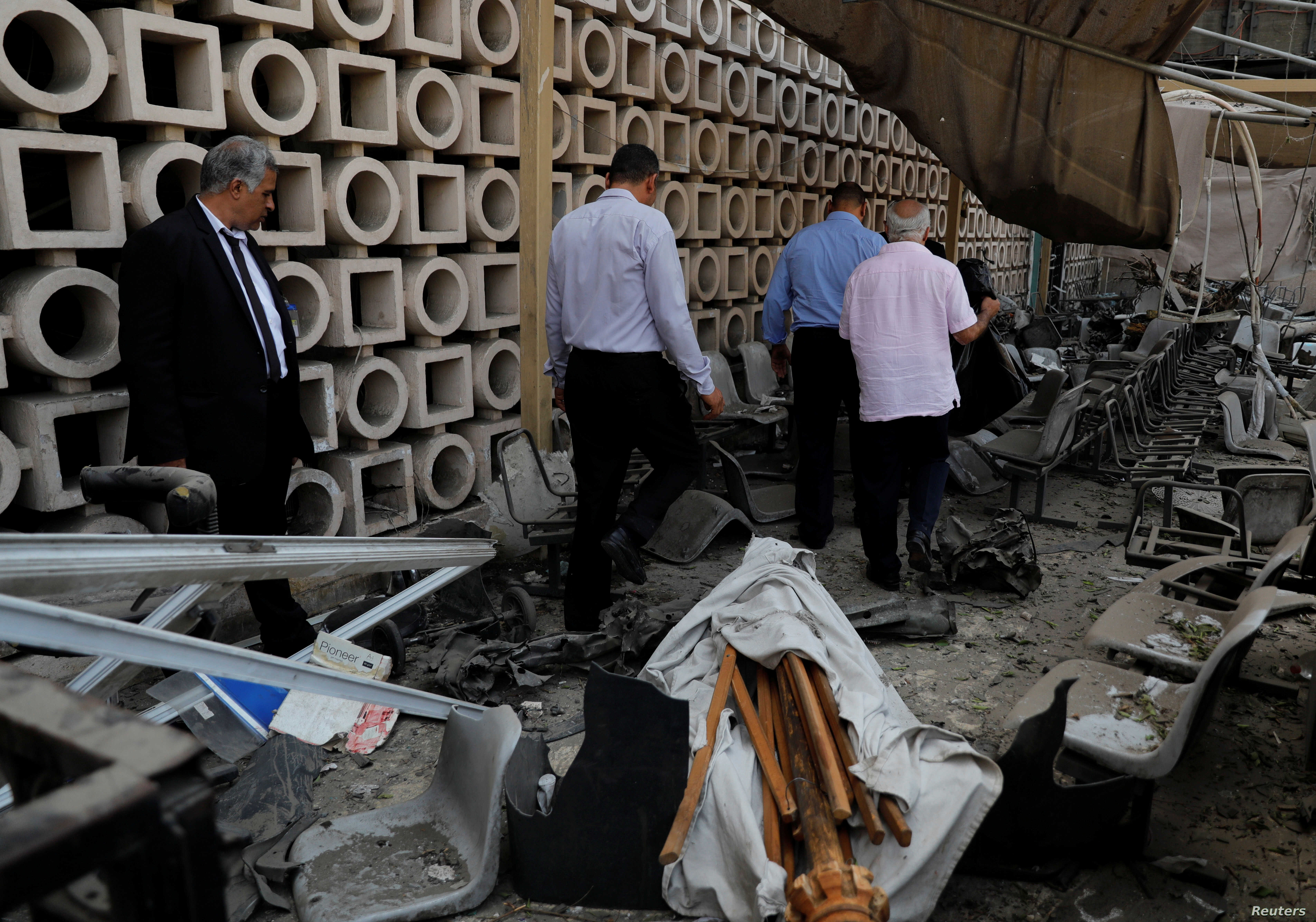 Egyptian investigators are seen in front of the damaged facade of the National Cancer Institute after an overnight fire from a blast, in Cairo, Egypt Aug. 5, 2019.