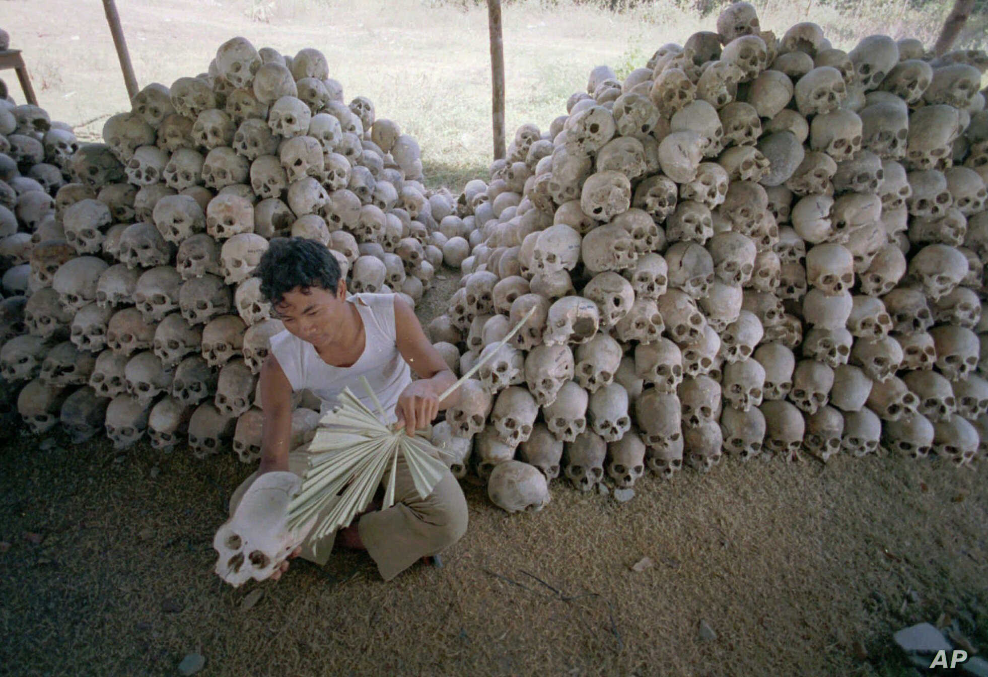 In this undated file photo, a man cleans a skull near a mass grave at the Chaung Ek torture camp that was run by Cambodia's Khmer Rouge.