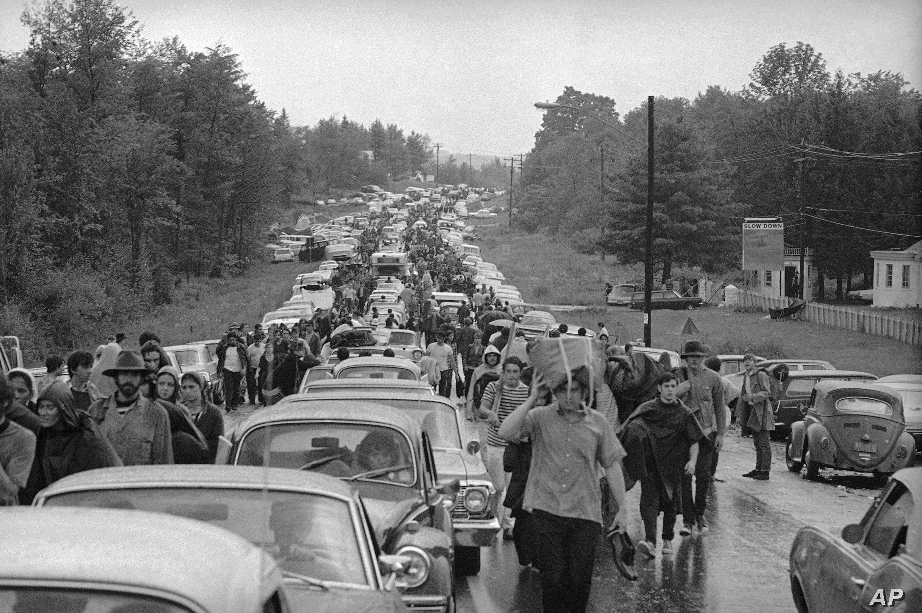 FILE - Hundreds of rock music fans jam a highway leading from Bethel, N.Y., as they try to leave the Woodstock Music and Art Festival, Aug. 16, 1969.