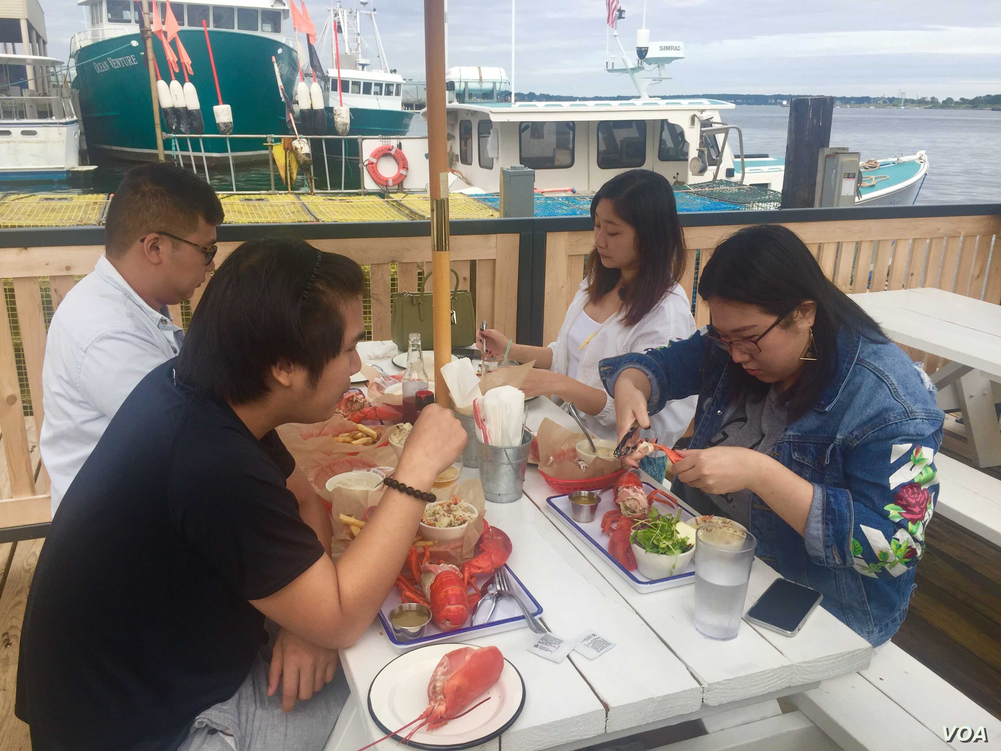 Chinese tourists feast on lobster in Maine. (J.Taboh/VOA)